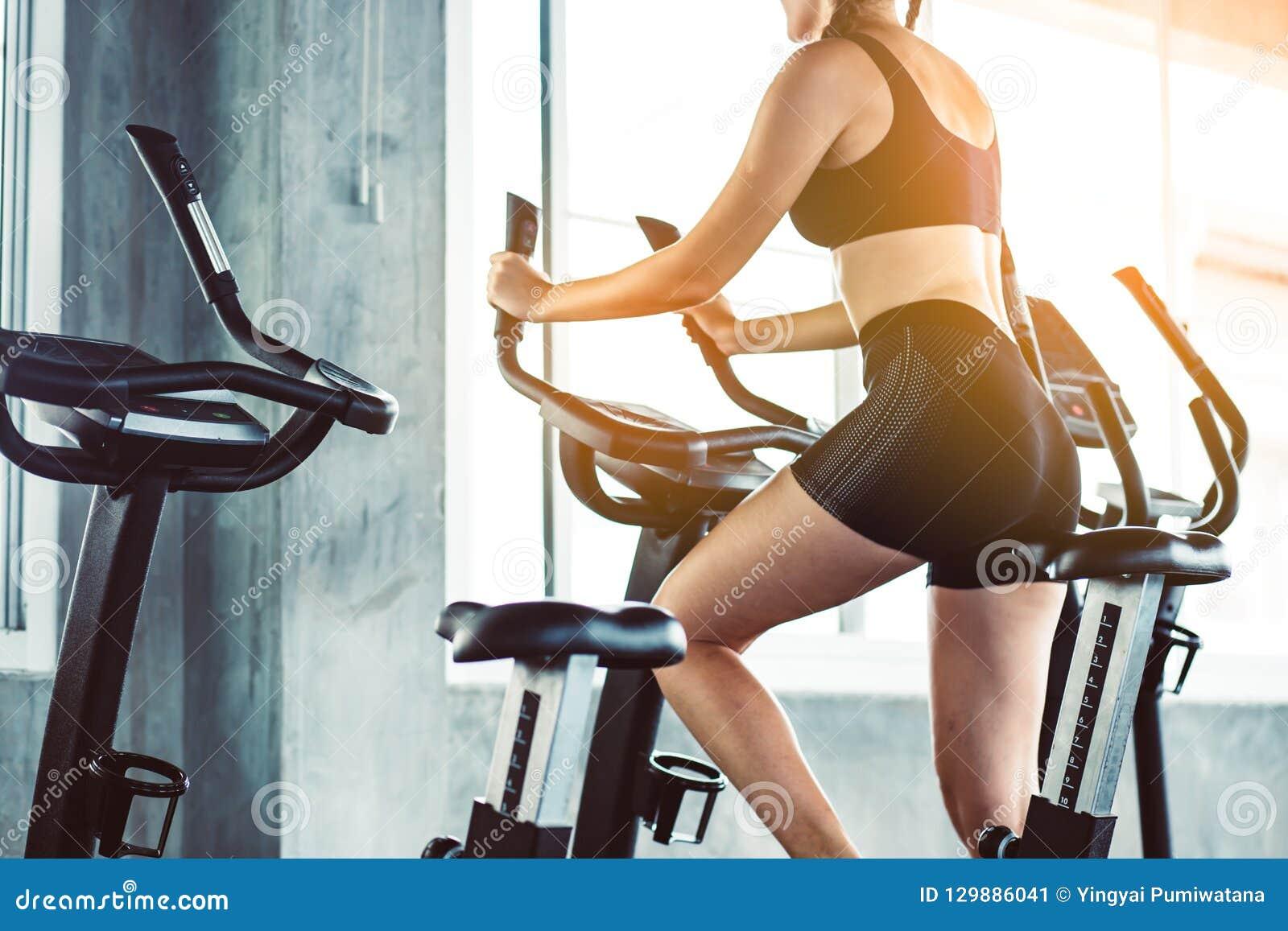 Женщина фитнеса в тренируя показывая тренировках с тренировкой-machin
