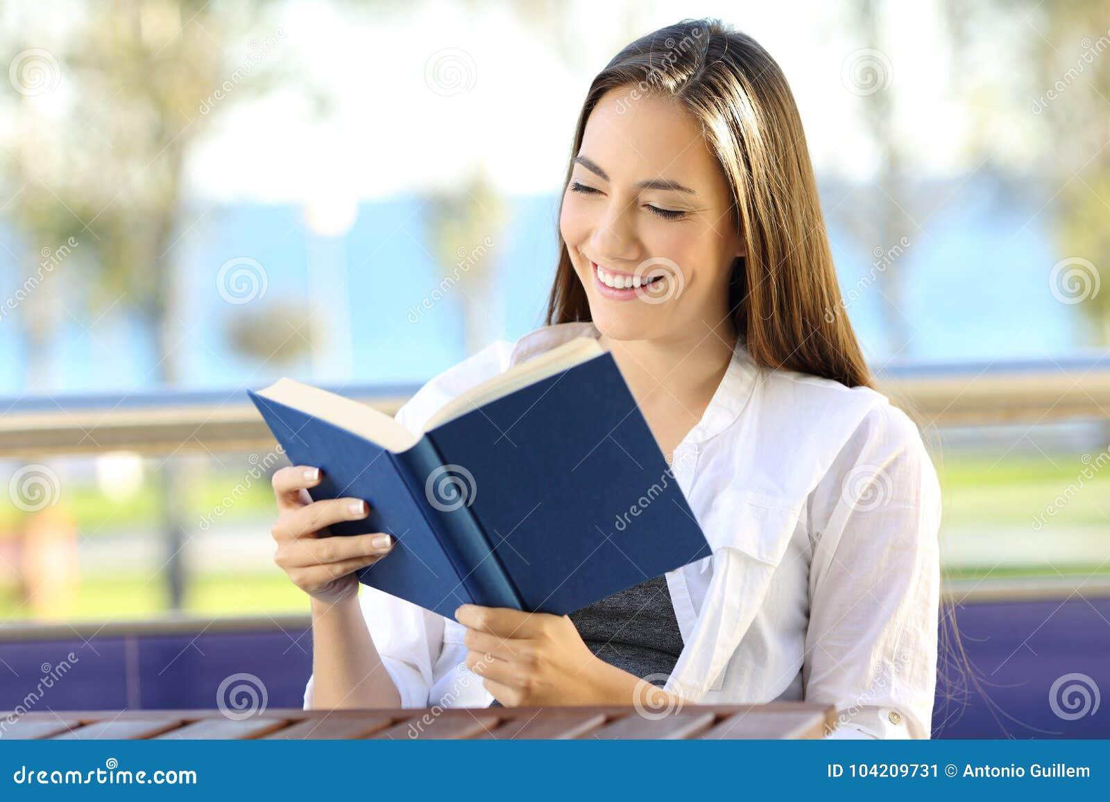Женщина читая книгу во время каникул на пляже
