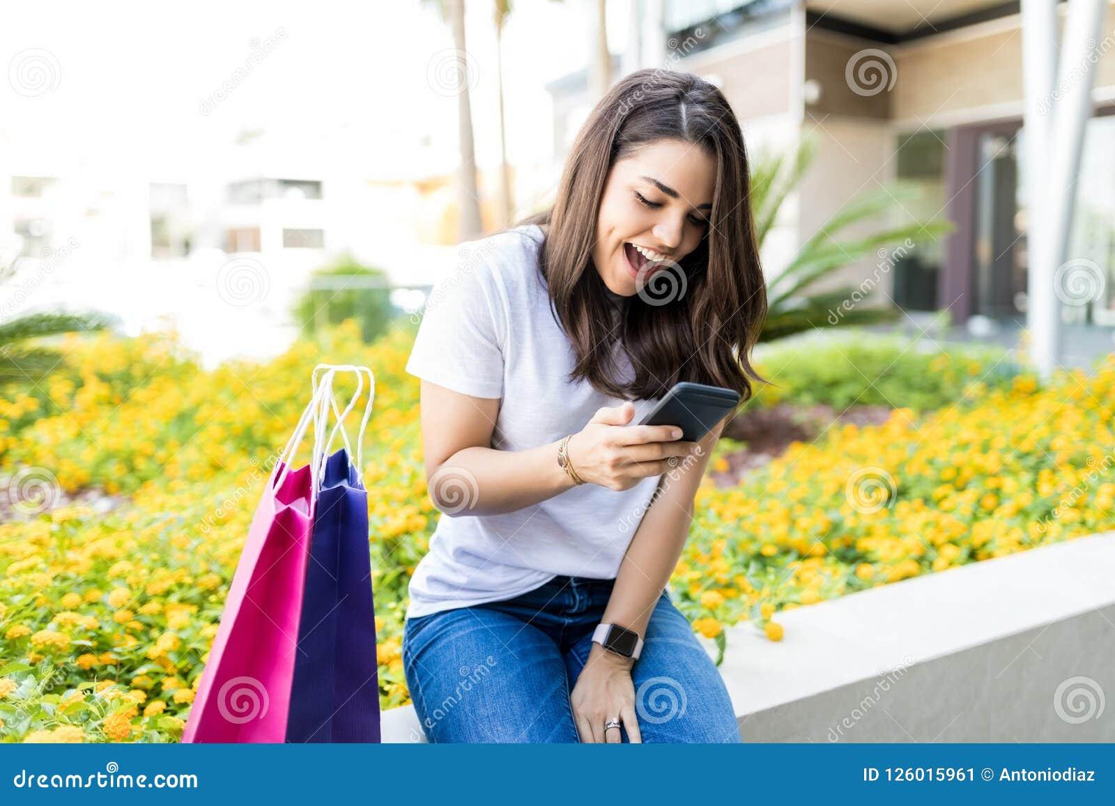 Женщина читая SMS на Smartphone хозяйственными сумками вне мола