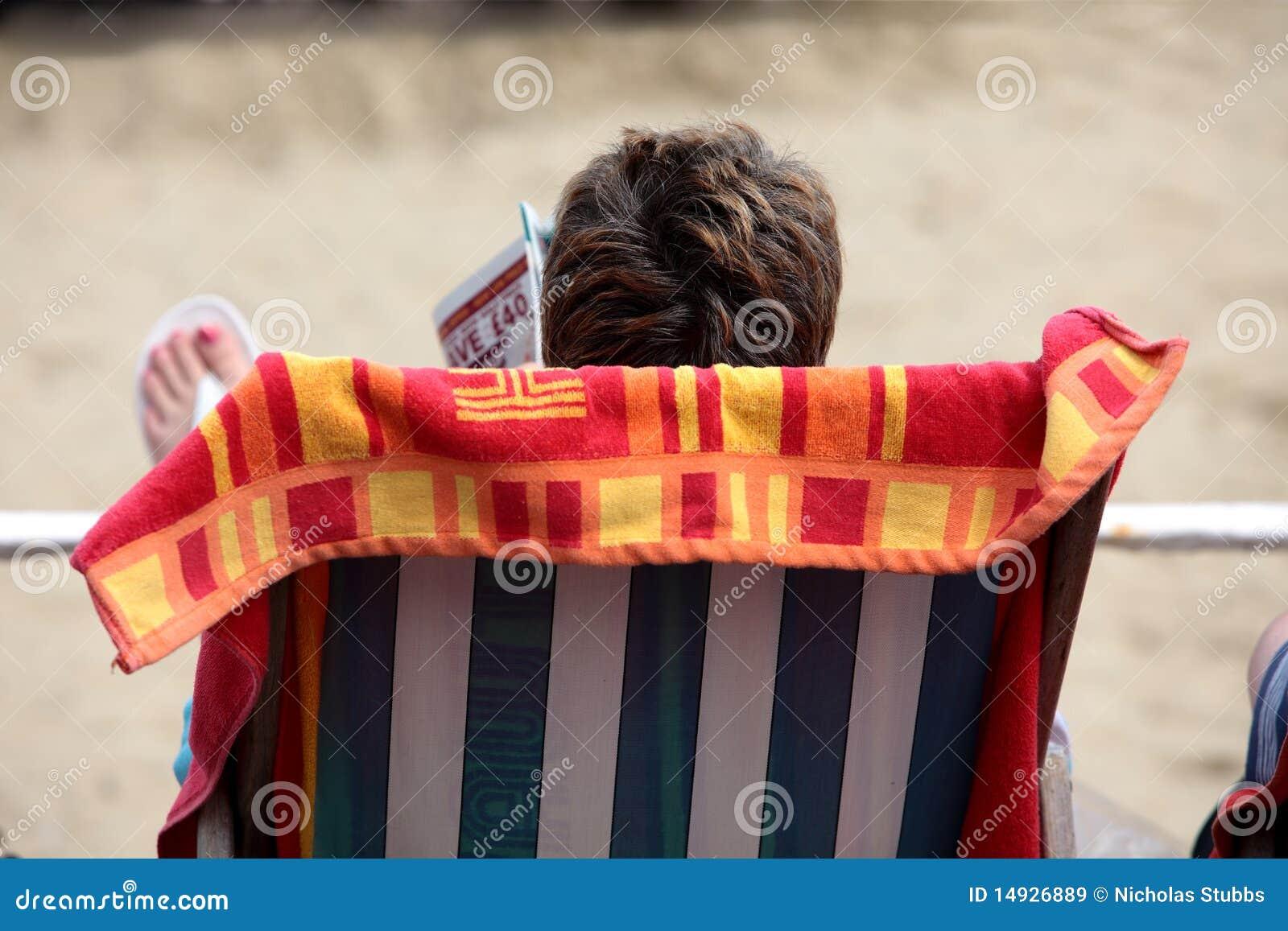 женщина чтения кассеты deckchair пляжа
