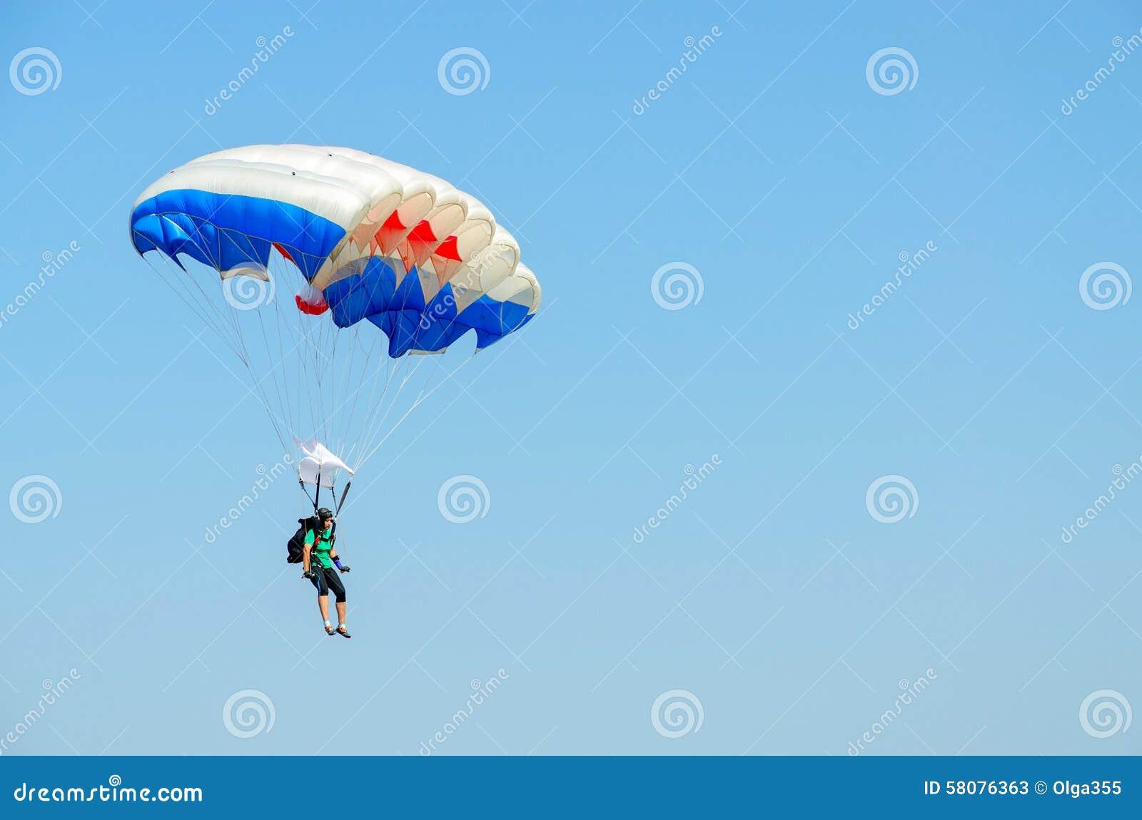 Женщина - skydiver выполняет спуск против безоблачного голубого неба