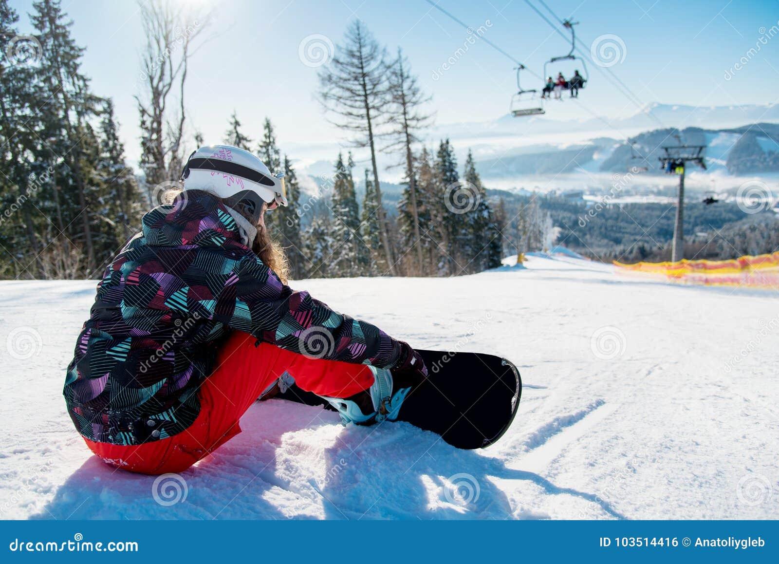 Женщина Snowboarder отдыхая на наклоне лыжи под подъемом