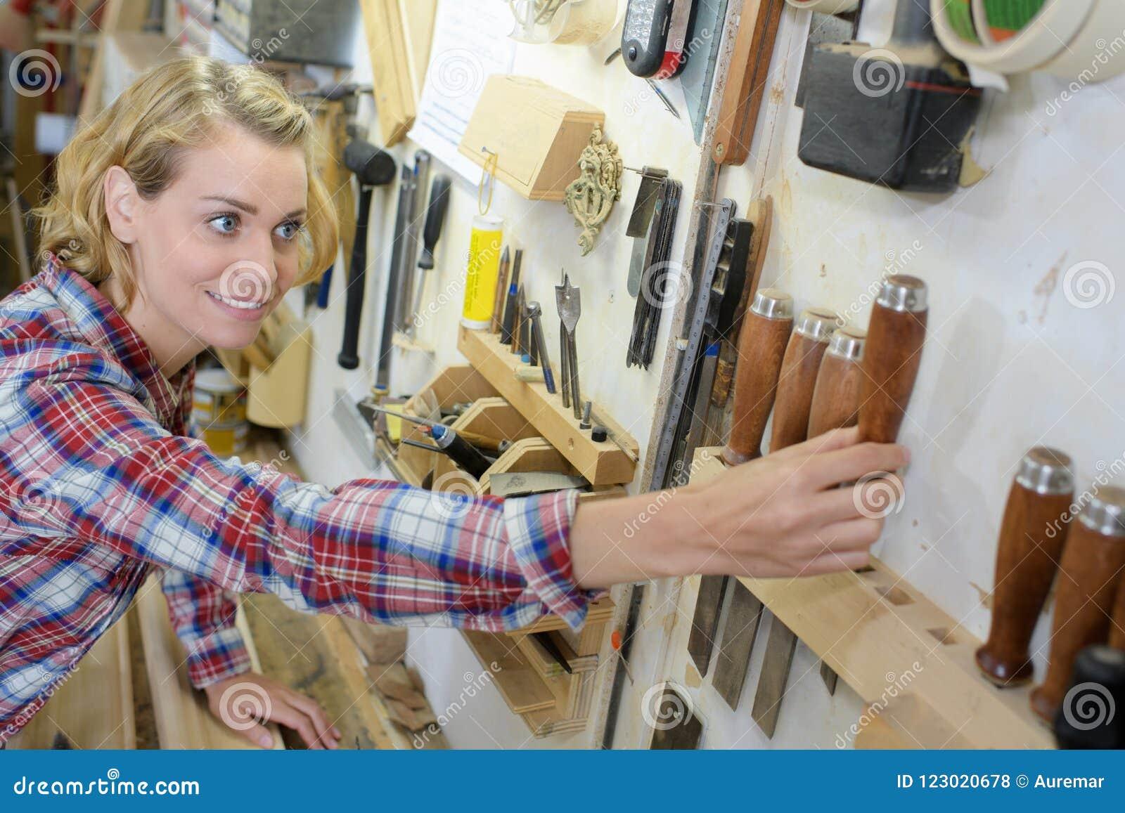 Женщина tidying вверх по мастерской