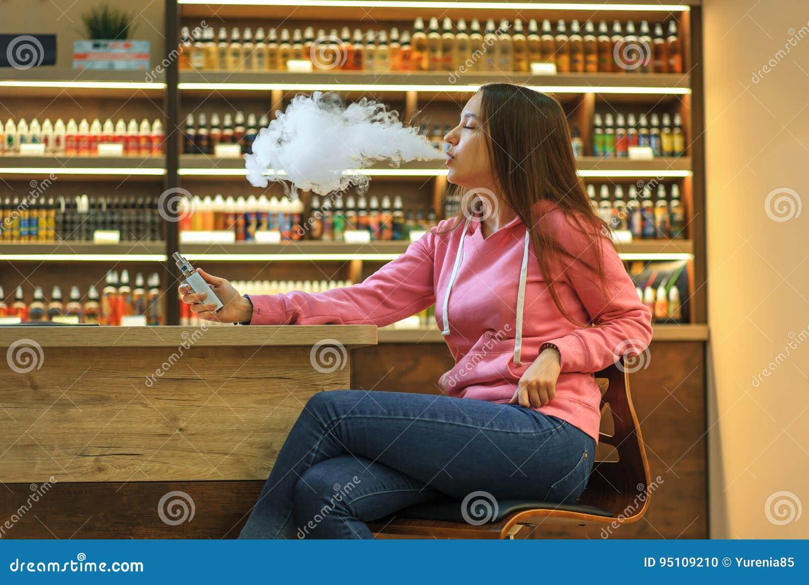 Женщина Vape Молодая милая девушка в розовом hoodie куря электронную сигарету