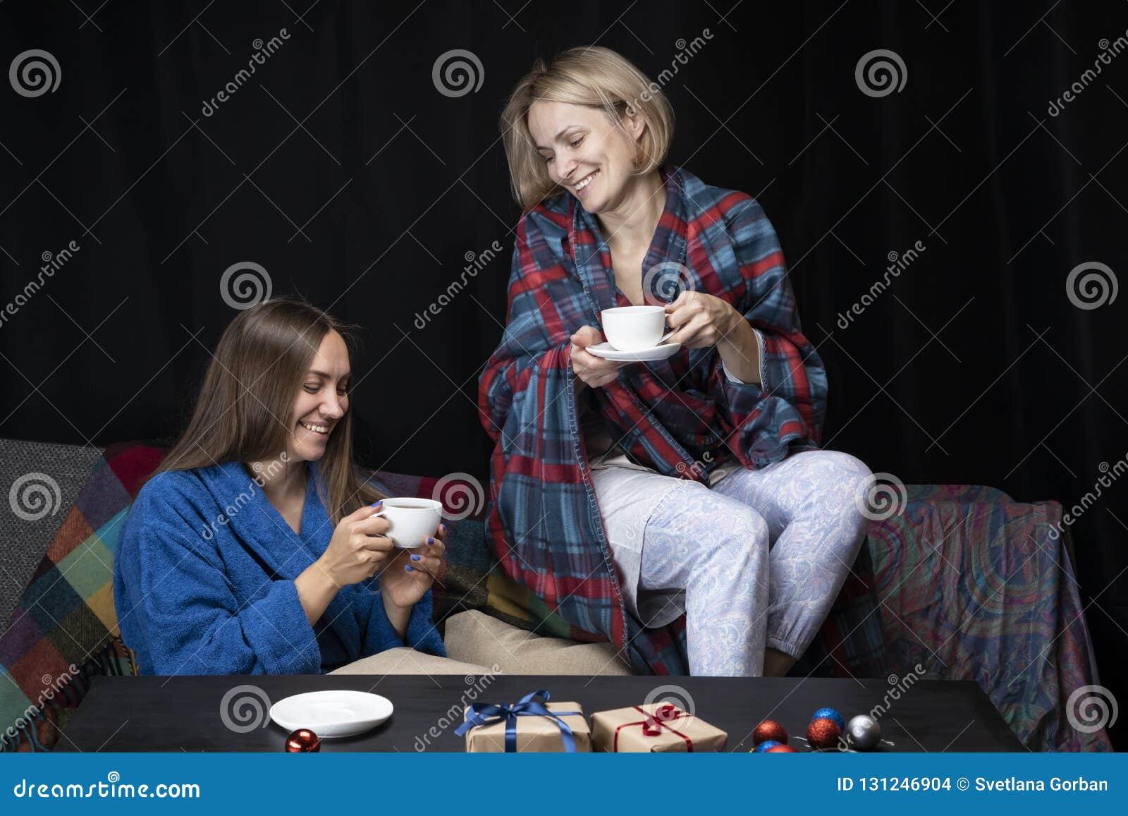 Женщины в домашних одеждах выпивают чай Черная предпосылка