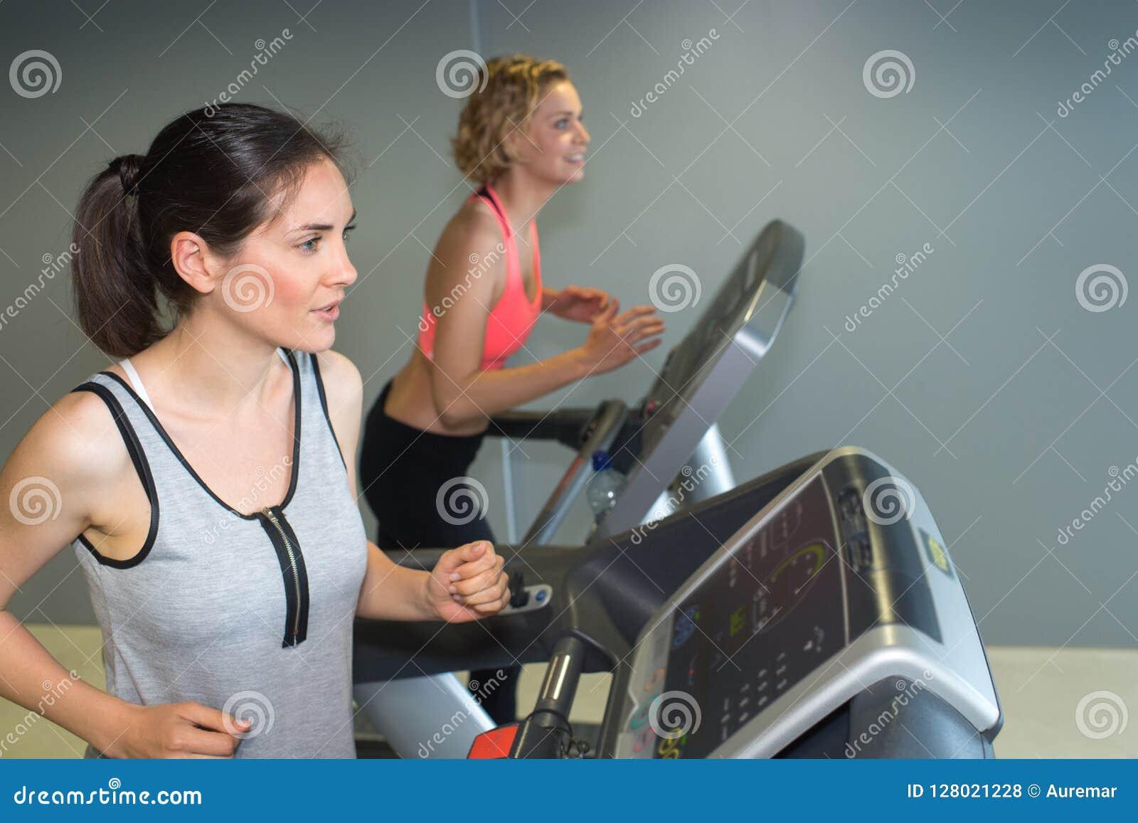 2 женщины ехать неподвижные велосипеды в современном клубе для женщин