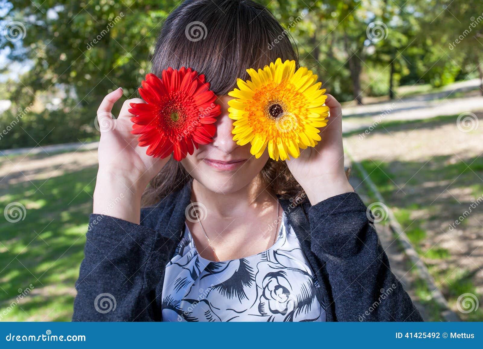 Женщины имея потеху пряча ее милые глаза 2 цветками