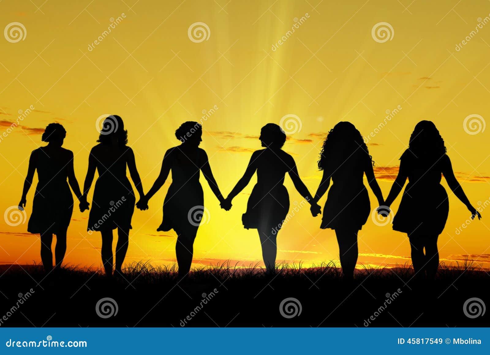 Женщины идя рука об руку