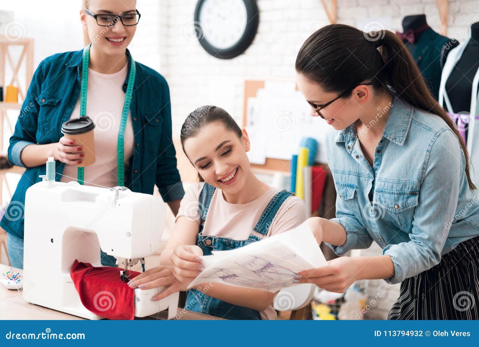 3 женщины на фабрике одежды Одно из их показывая светокопию