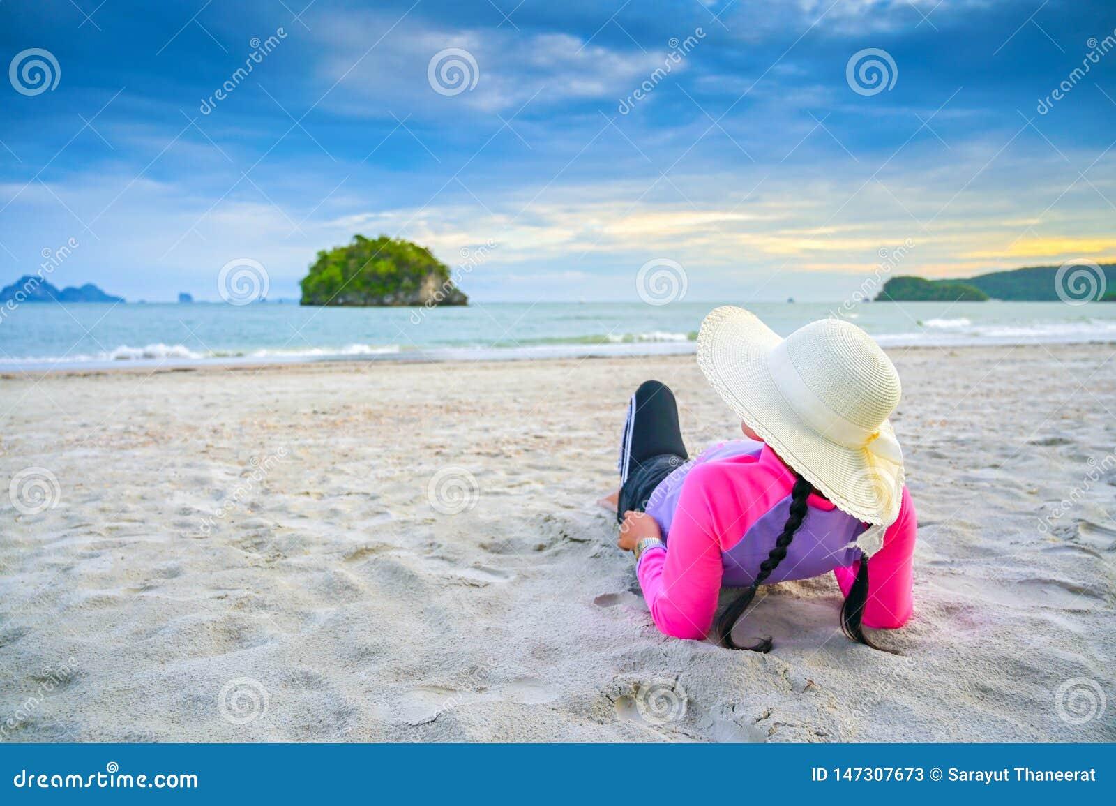Женщины нося шляпы спят на море пляжа