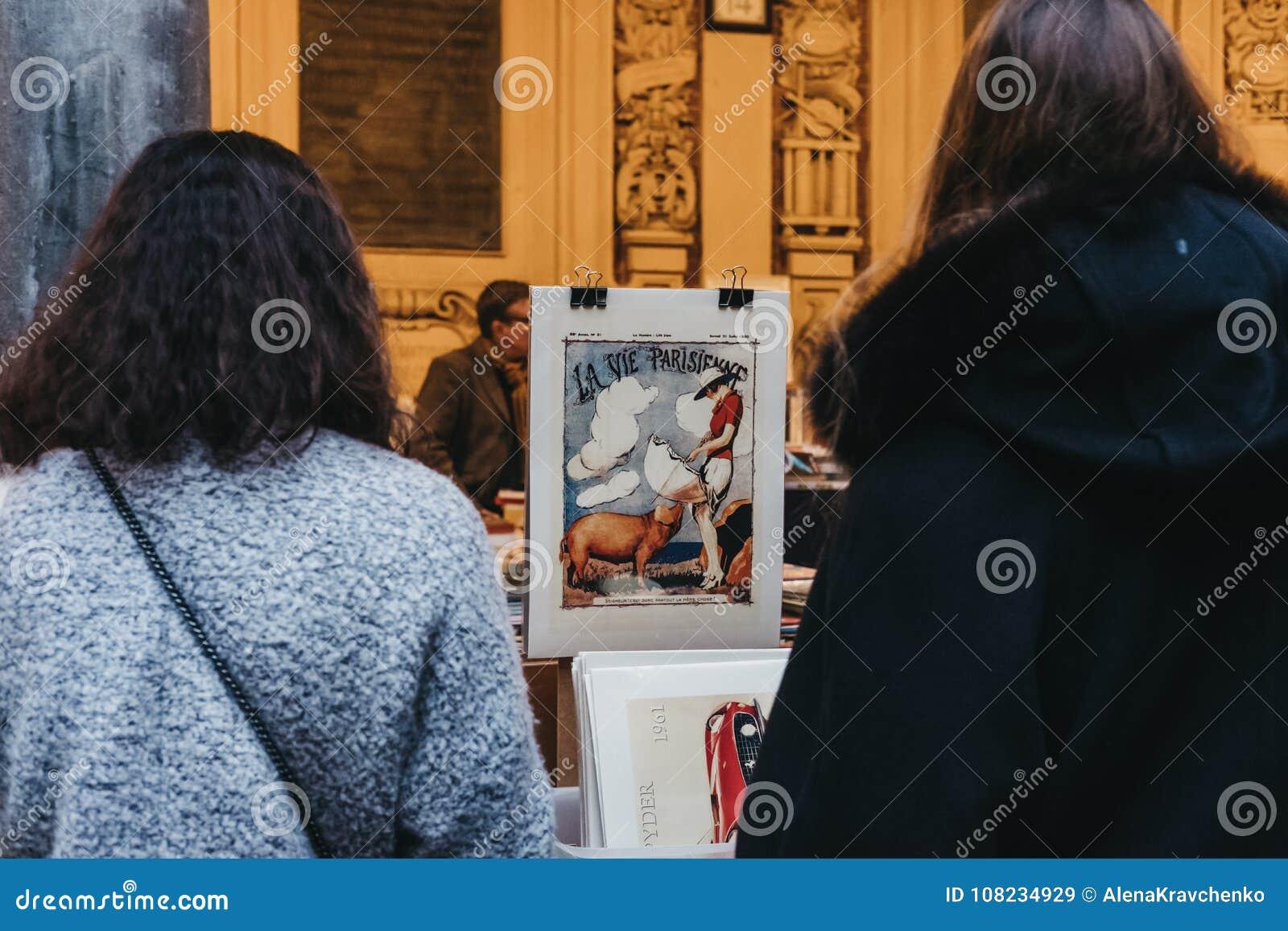 Женщины просматривают ретро рынок книги плакатов из вторых рук в дворе обмена старого запаса фондовой биржи Vieille в Лилле, Фран