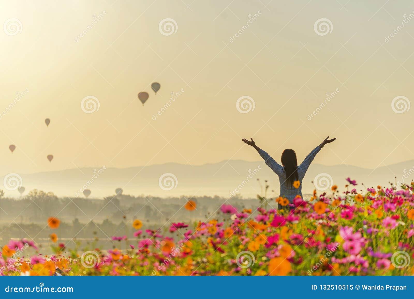 Женщины путешественника образа жизни поднимают чувство руки хорошее ослабляют и счастливая свобода и видят воздушный шар огня