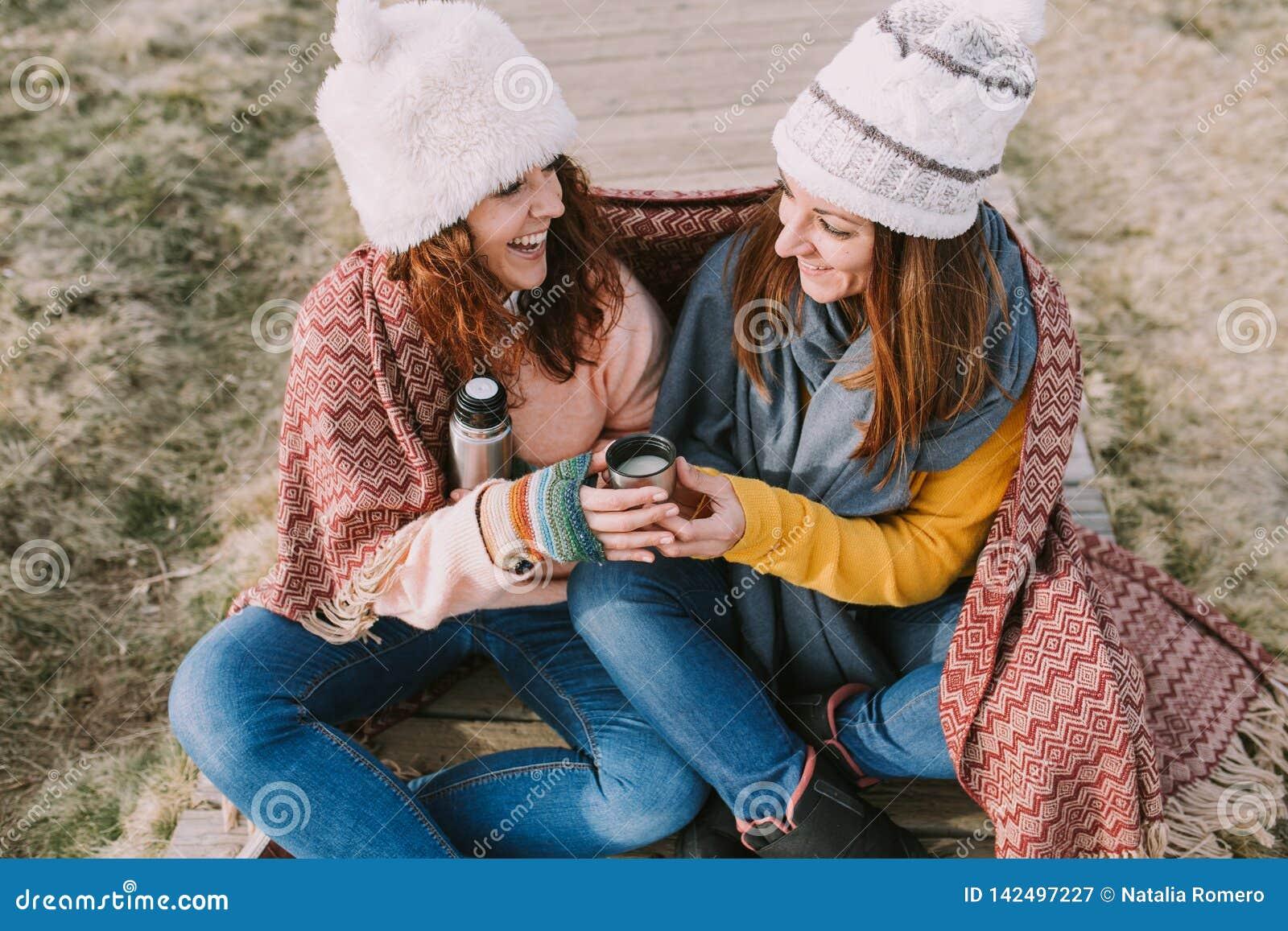 2 женщины смеются совместно пока они выпивают чашку горячего отвара