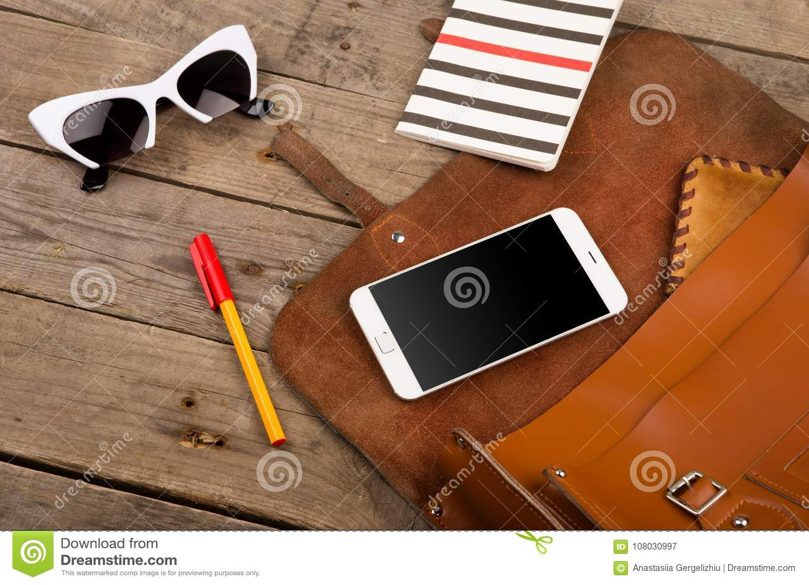 женщины установили с сумкой, умным телефоном, солнечными очками, блокнотом, ручкой и портмонем на коричневом деревянном столе