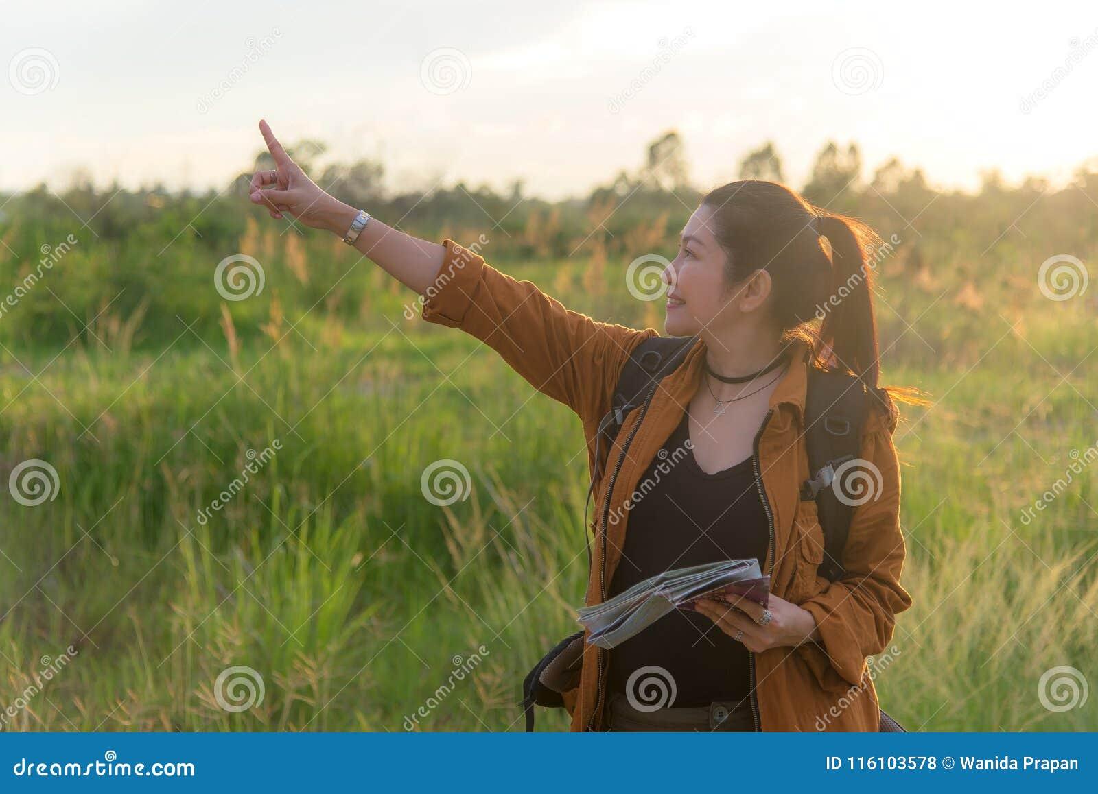 Женщины Hiker азиатские идя в национальный парк с рюкзаком Располагаться лагерем туриста женщины идя в лесе луга, земле захода со