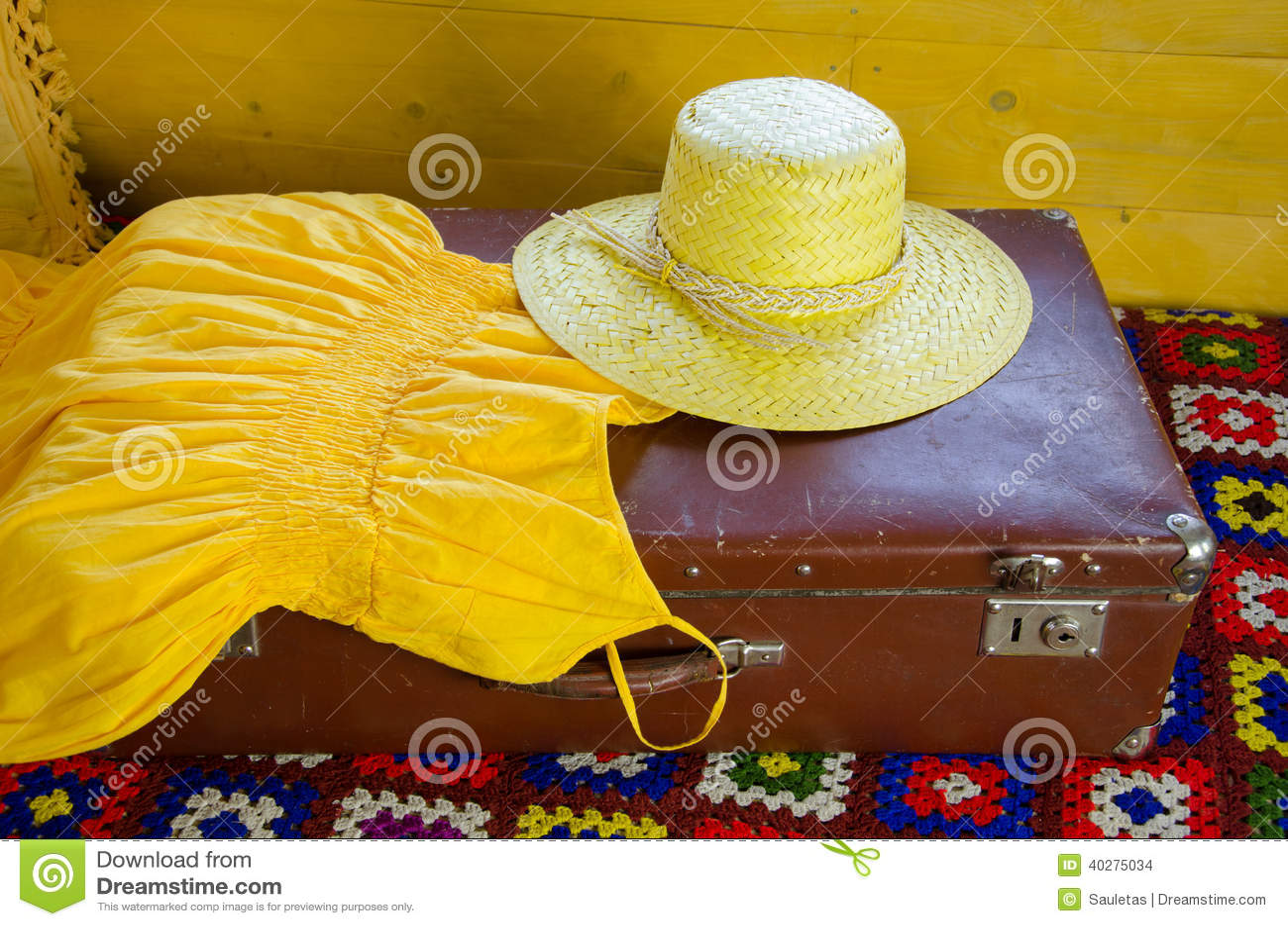Желтое платье и соломенная шляпа лежа на старом чемодане