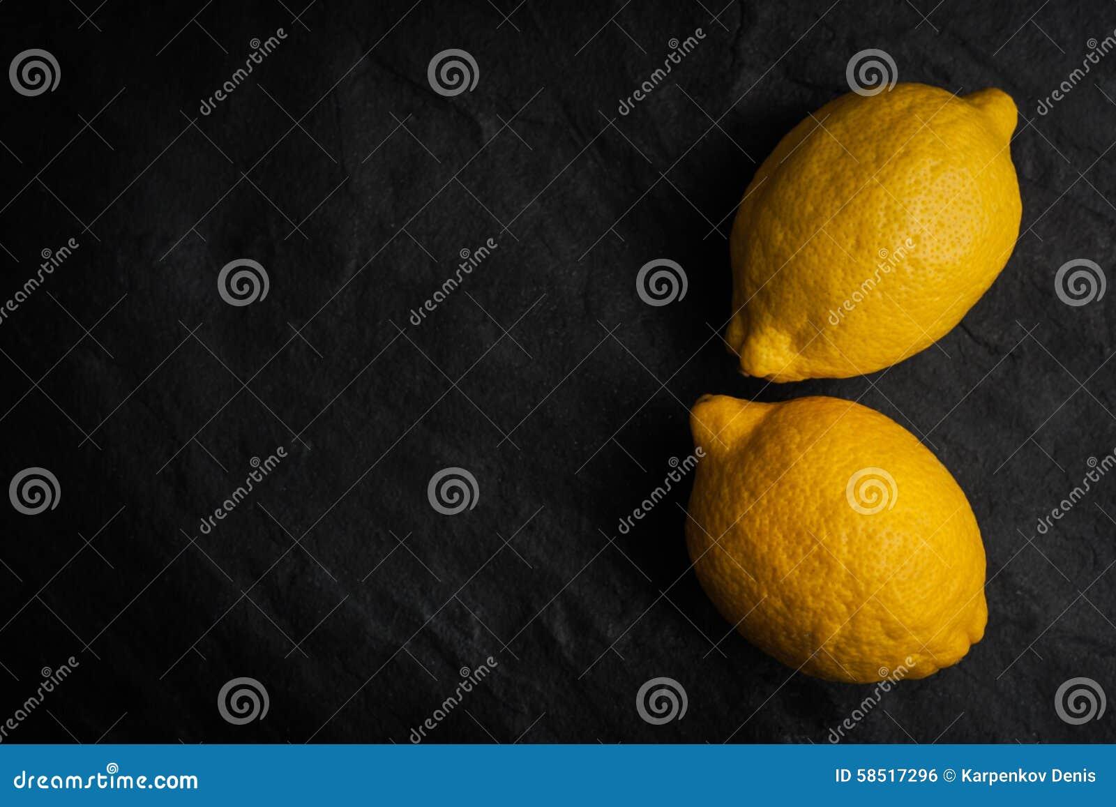 Желтые лимоны на черной каменной таблице горизонтальной