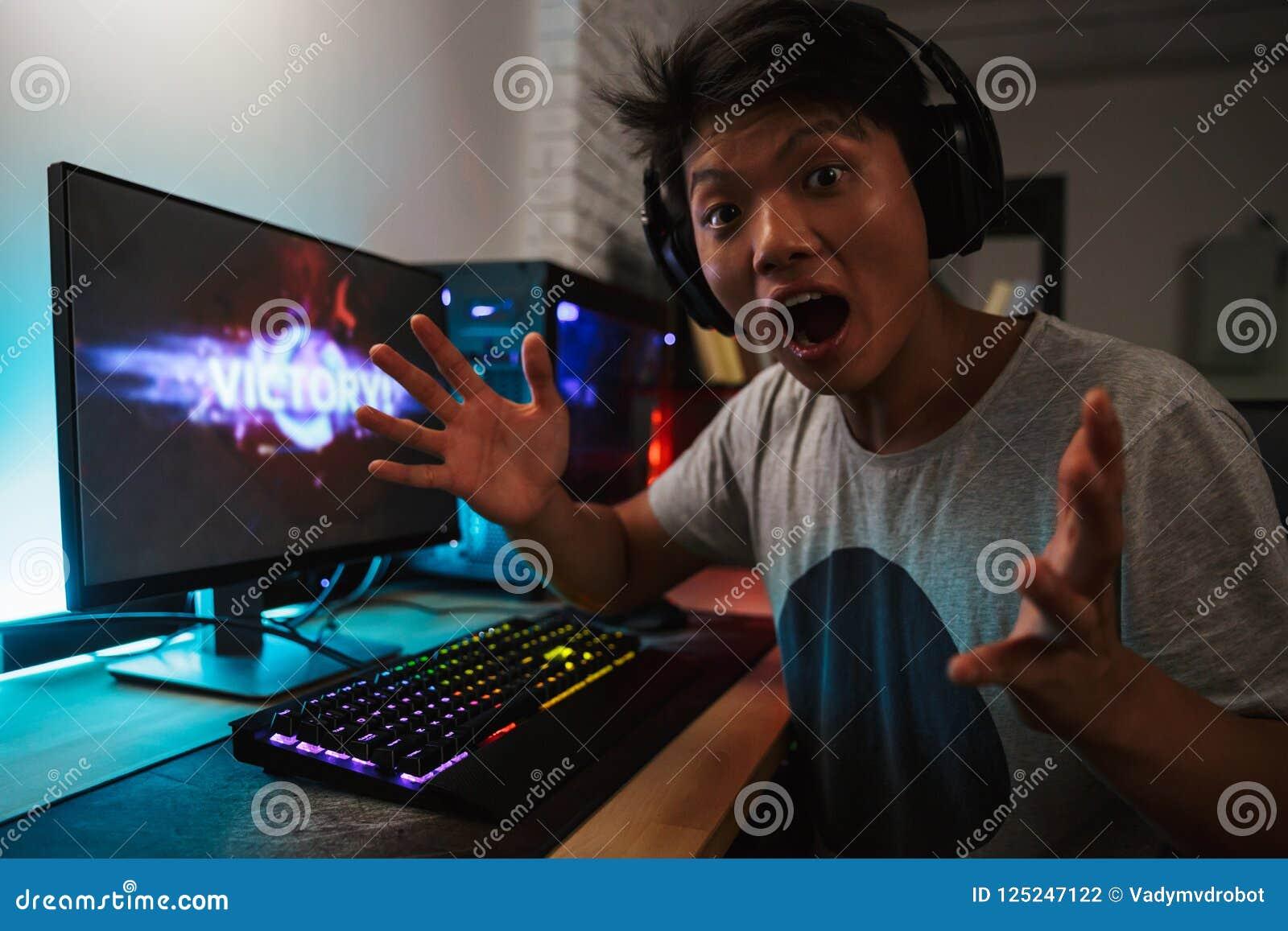 Жизнерадостная азиатская победа ликования мальчика gamer пока играющ видео g