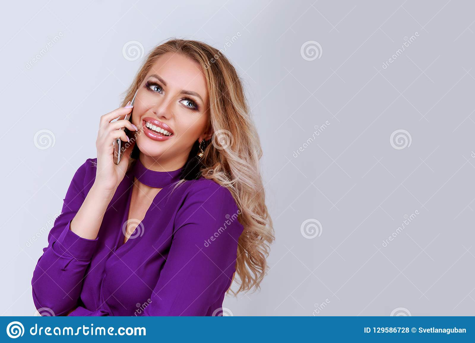 Жизнерадостная белокурая женщина говоря на смартфоне