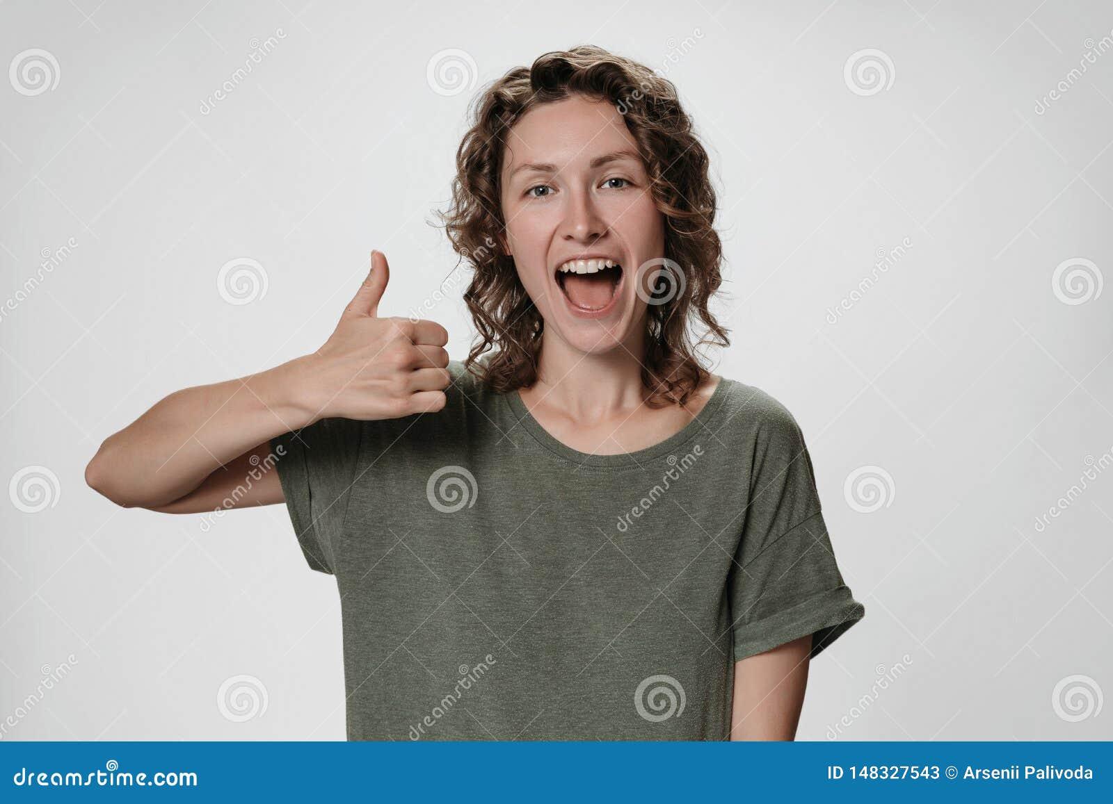 Жизнерадостная восторженная молодая курчавая женщина с раскрывает глаза и рот широко показывая