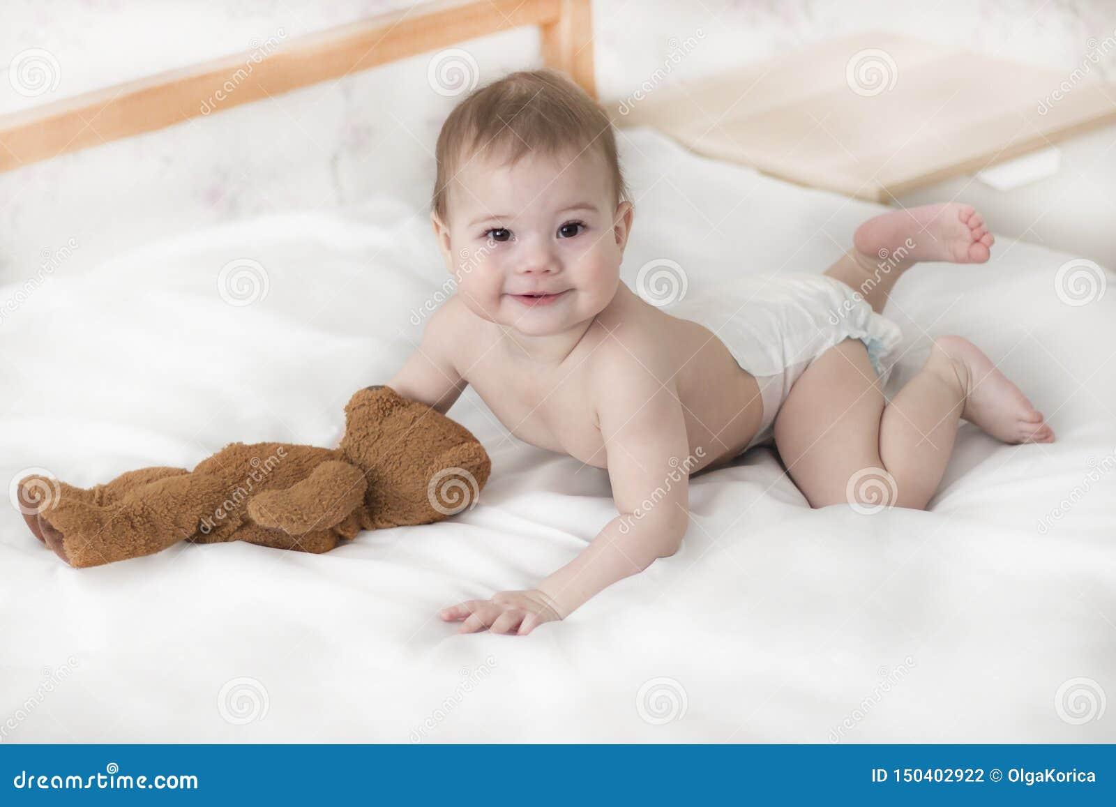 Жизнерадостная девушка ребенка в пеленке лежа с плюшевым мишкой Милый младенец в пеленке вползая на кровати, взгляд в камеру