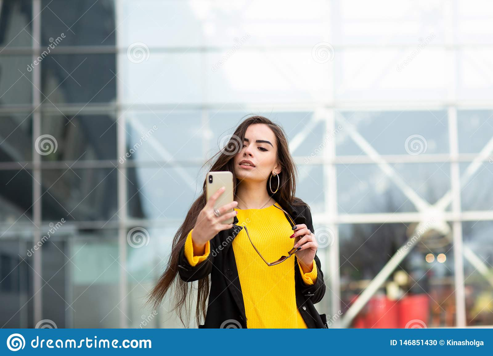 Жизнерадостная женщина брюнета в желтом свитере делая sefie против предпосылки аэропорта :