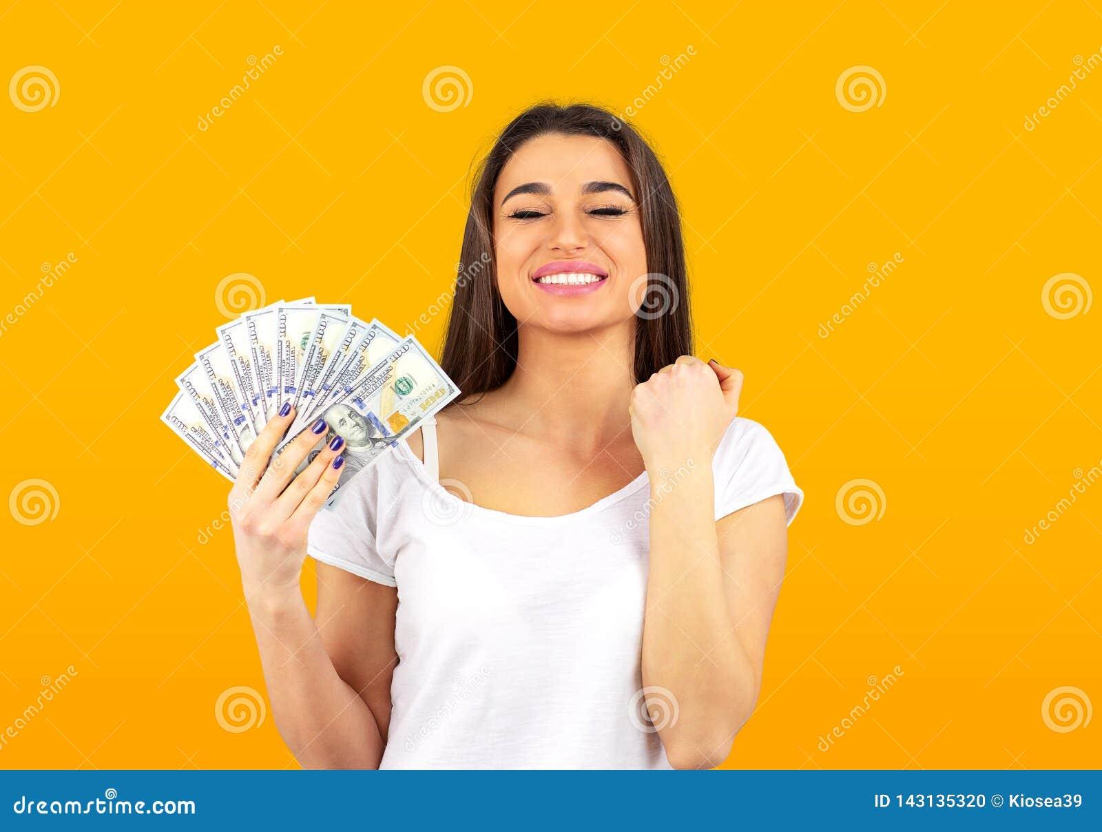 Жизнерадостная женщина держа деньги и празднуя успех