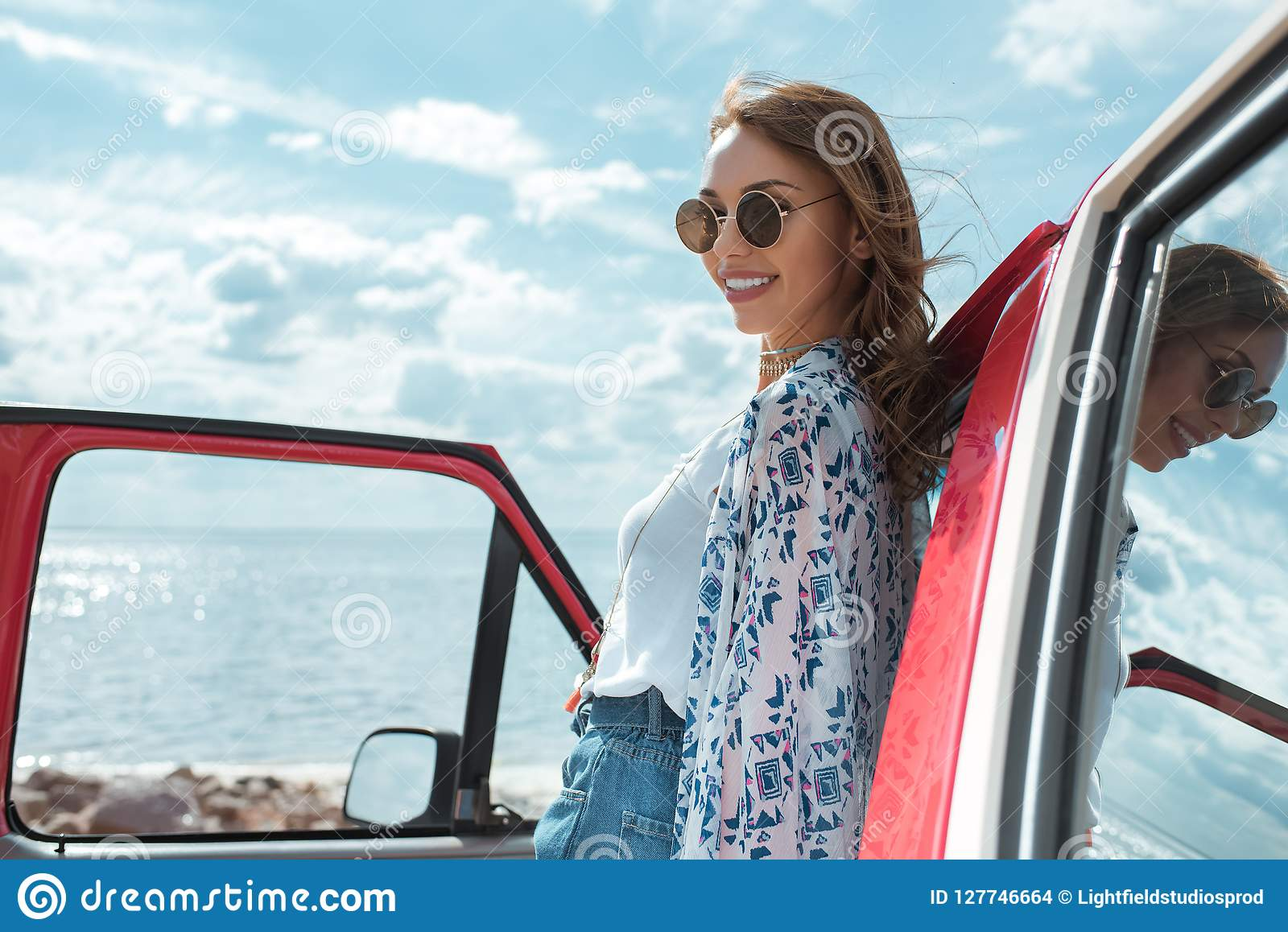 Жизнерадостная молодая женщина в солнечных очках