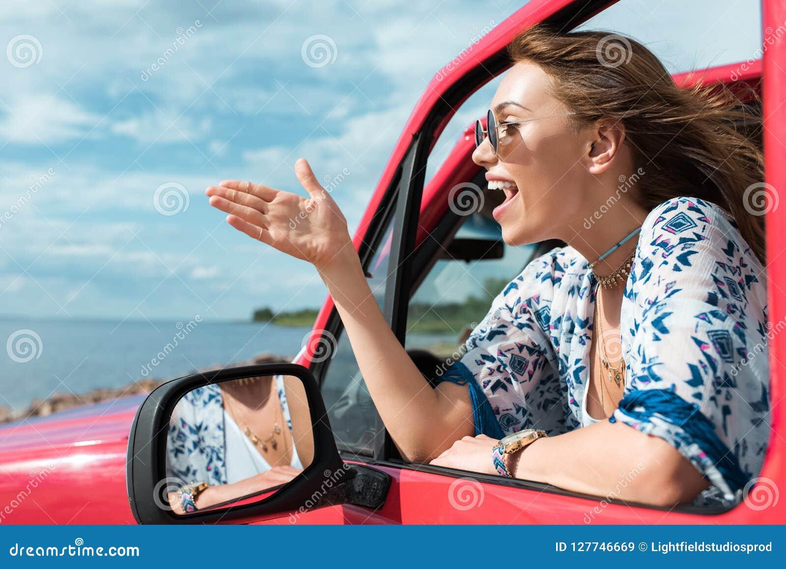 жизнерадостная молодая женщина показывая жестами и говоря в автомобиле