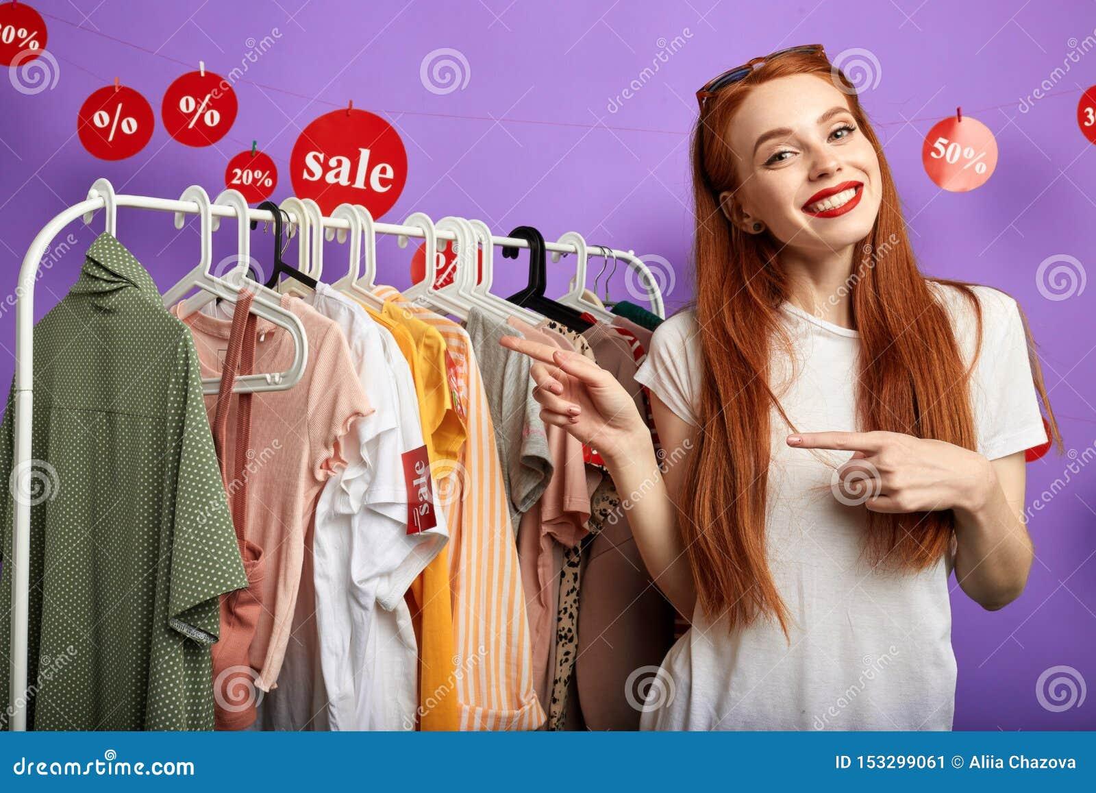 Жизнерадостная молодая очаровательная девушка указывая на одежды