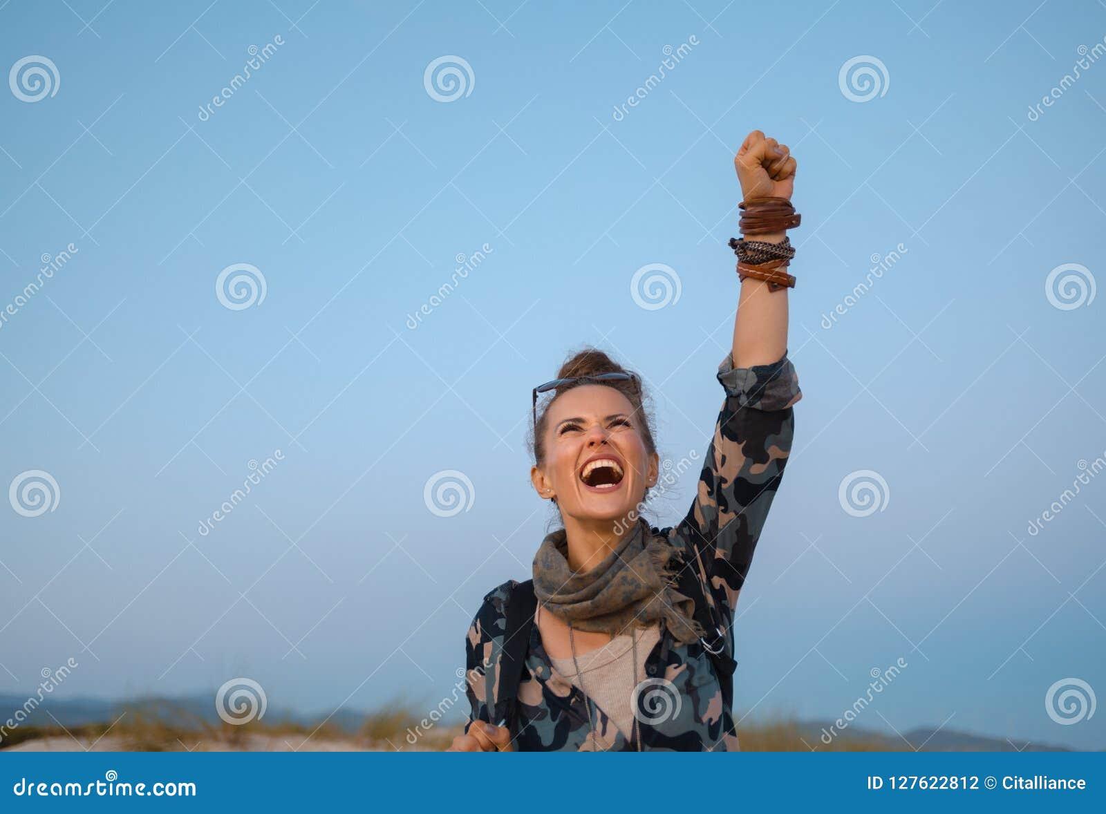 Жизнерадостное здоровое ликование женщины путешественника против голубого неба