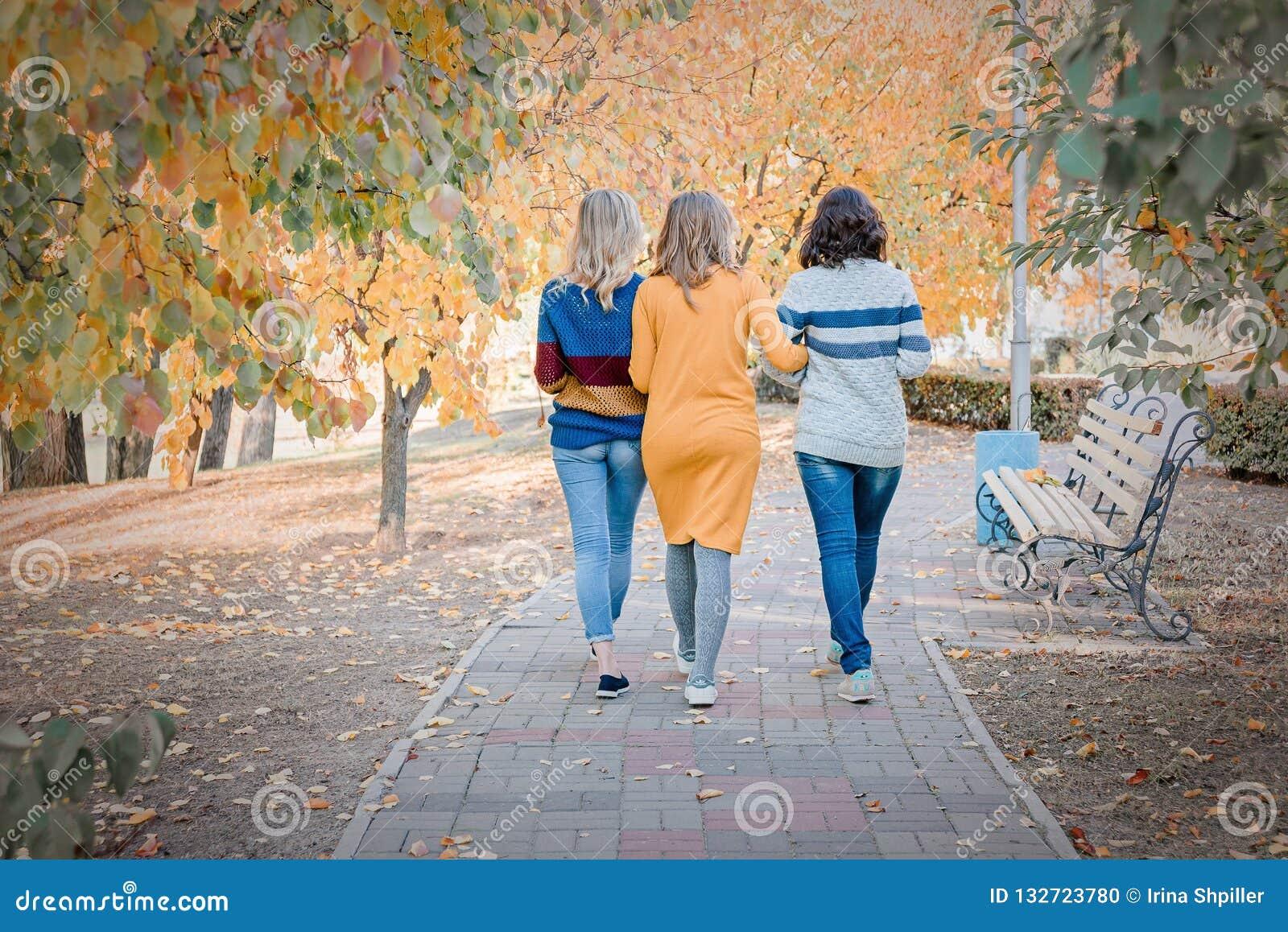Жизнерадостные привлекательные 3 лучшего друга молодых женщин идя и имея потеха совместно снаружи