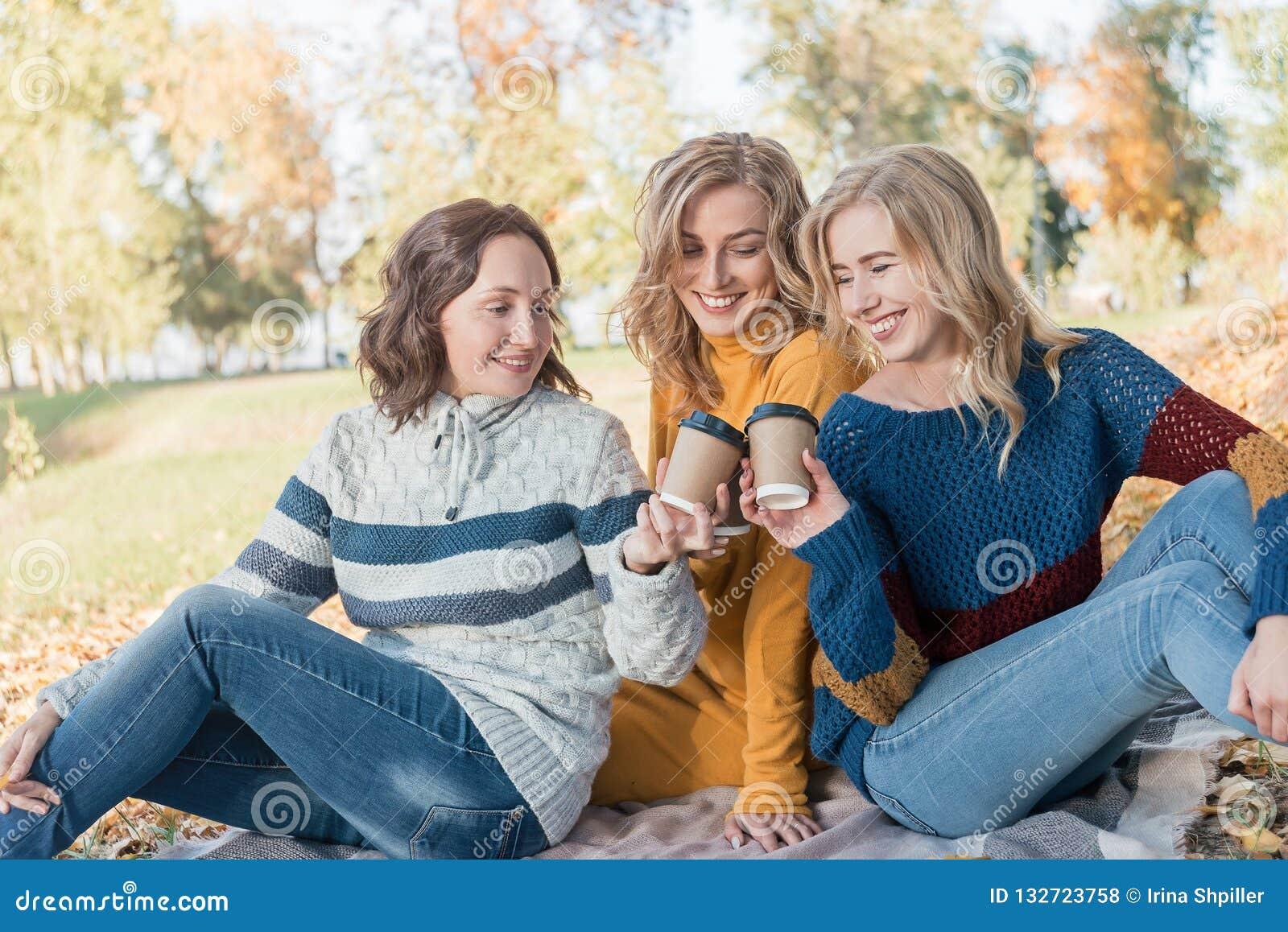 Жизнерадостные привлекательные 3 лучшего друга молодых женщин имея пикник и потеху совместно снаружи