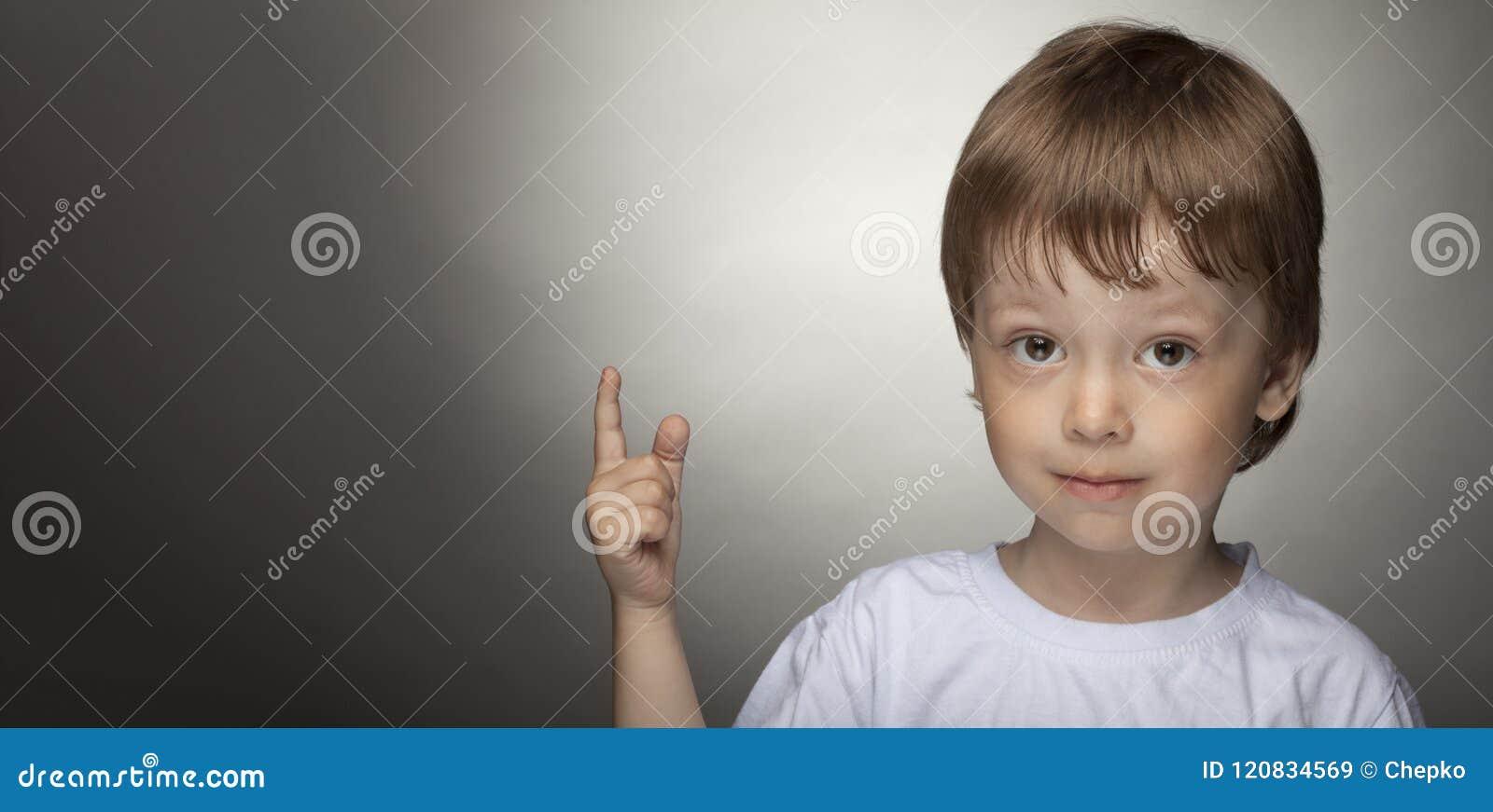 Жизнерадостный мальчик указывая вверх, счастливый ребенок с хорошей идеей