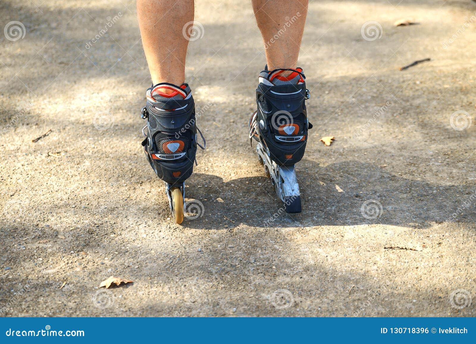 Жизнерадостный sporty человек 50-55 лет едущ кататься на коньках ролика в парке в сезоне осени, rollerblading как здоровая тренир
