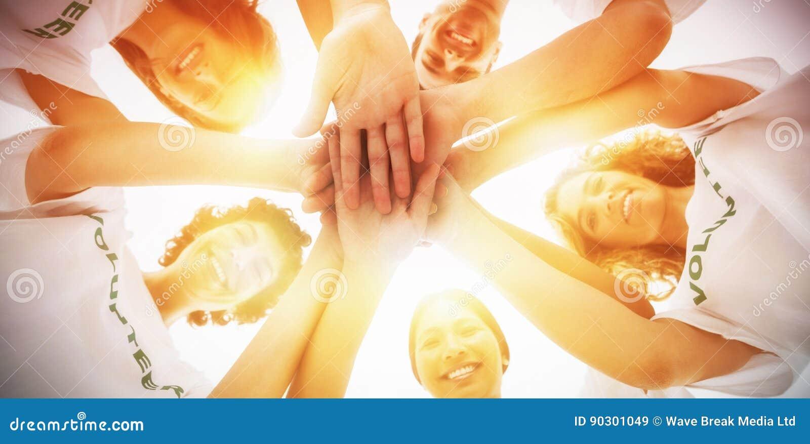 Жизнерадостная группа в составе волонтеры кладя руки совместно