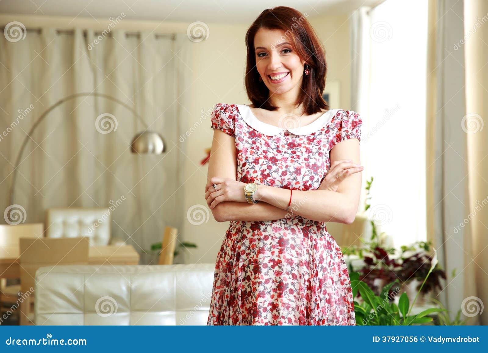 Жизнерадостная женщина стоя при сложенные оружия