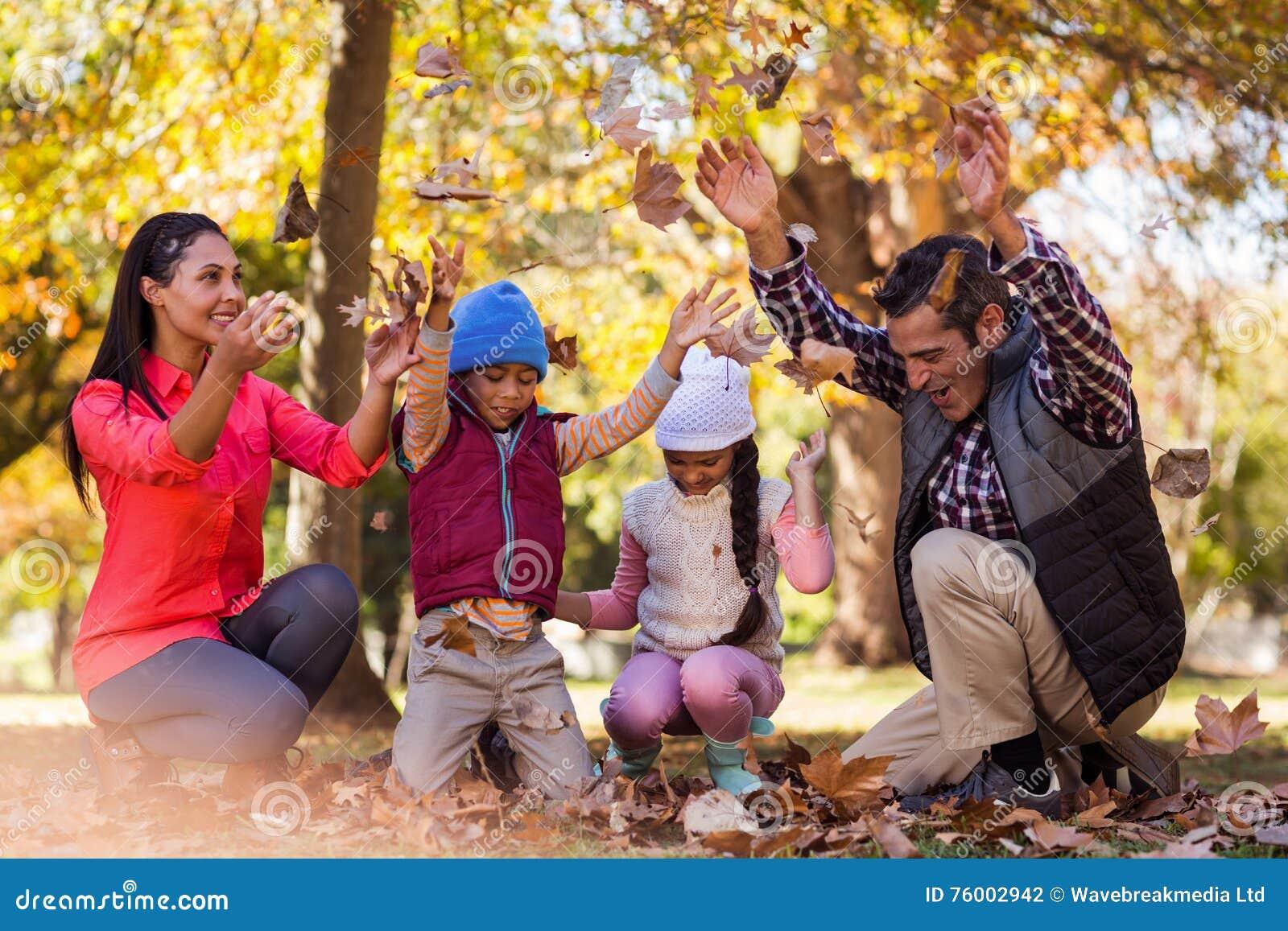 Жизнерадостная семья играя с листьями осени