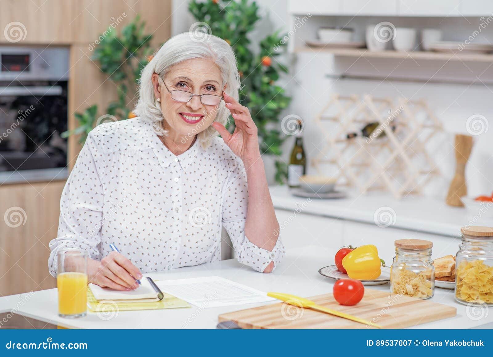 Жизнерадостная старшая домохозяйка высчитывая отечественные расходы