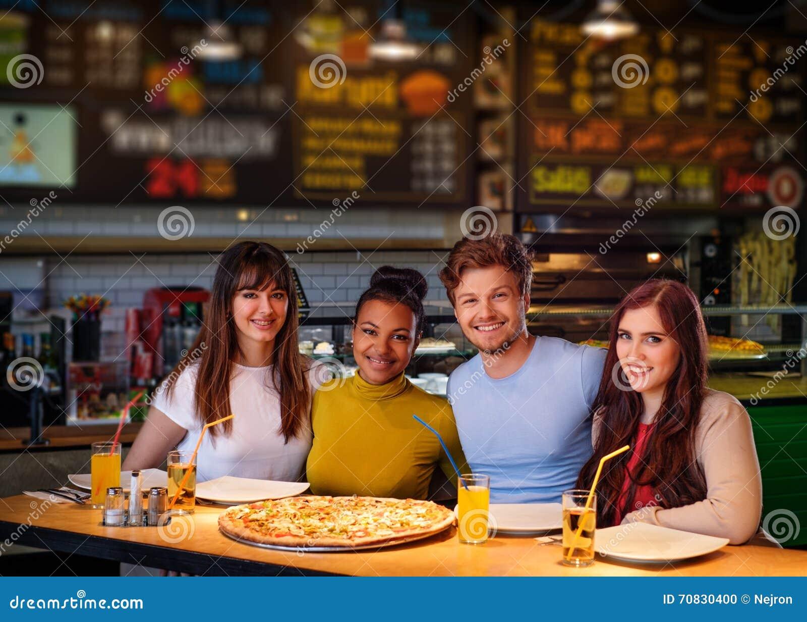 Жизнерадостные multiracial друзья имея потеху есть в пиццерии
