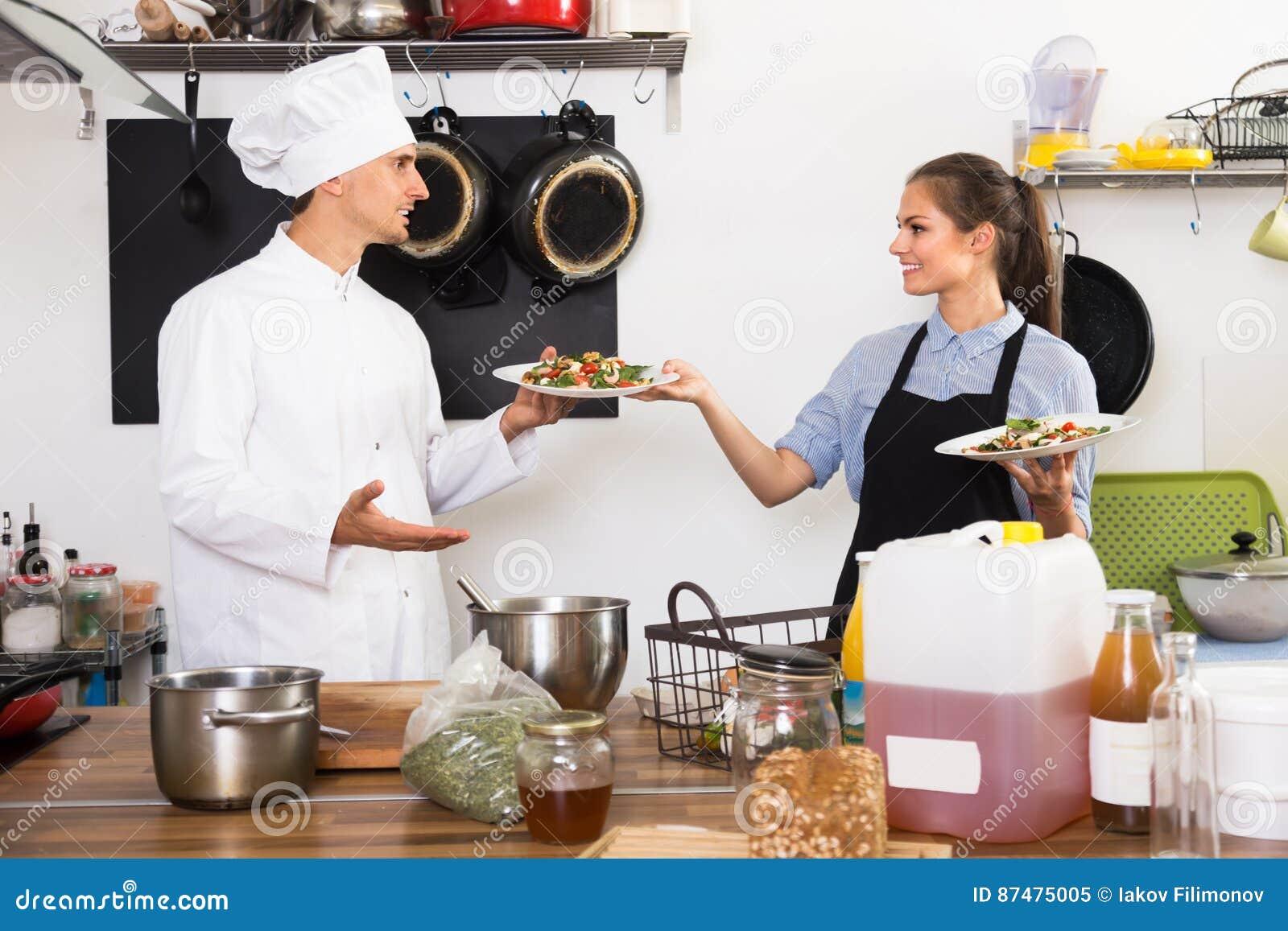 Жизнерадостный кашевар человека давая салат к официантке