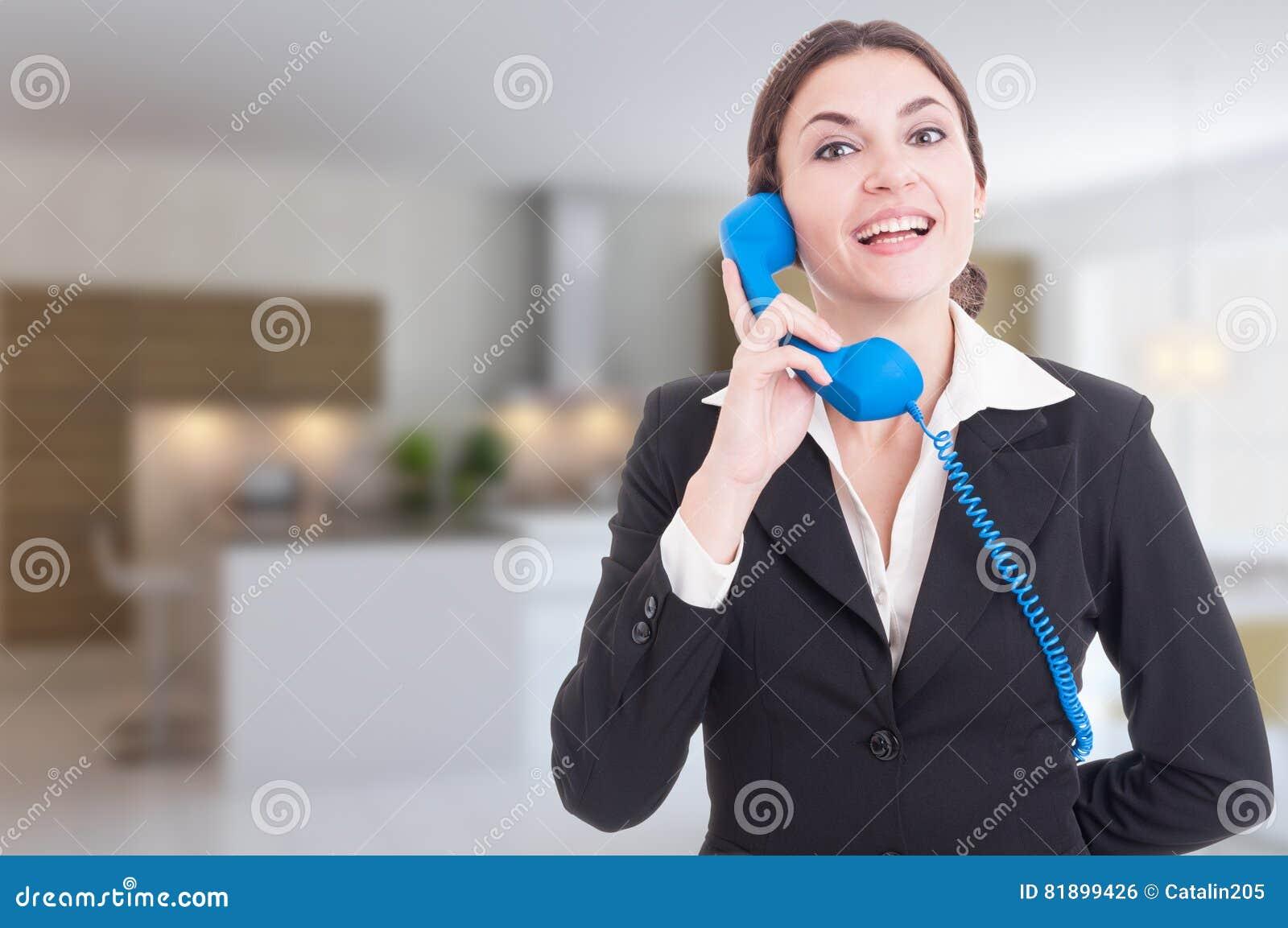 Жизнерадостный риэлтор женщины имея переговор на телефоне