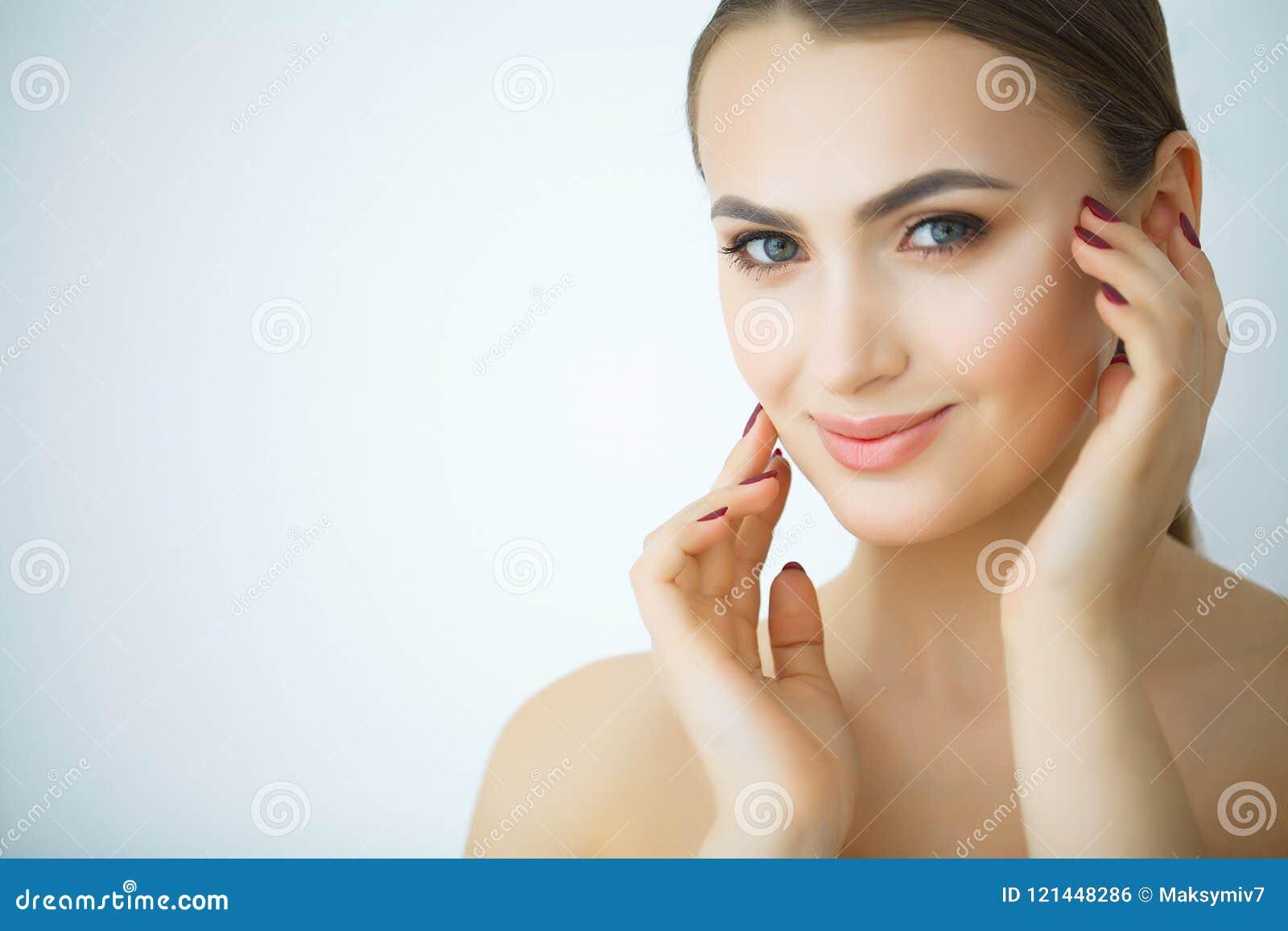 Забота кожи красоты Красивая женщина прикладывая косметическую сливк стороны