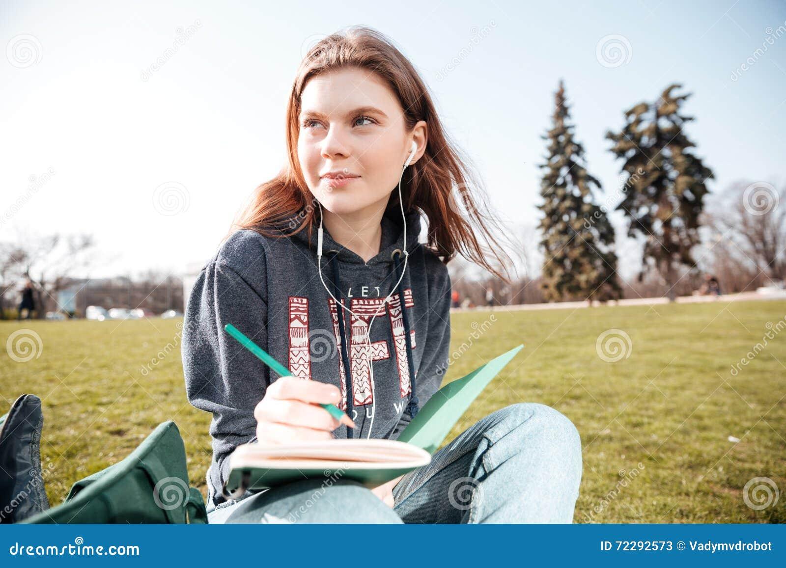 Download Заботливая женщина в наушниках сидя и писать в тетради Outdoors Стоковое Изображение - изображение насчитывающей портрет, люди: 72292573