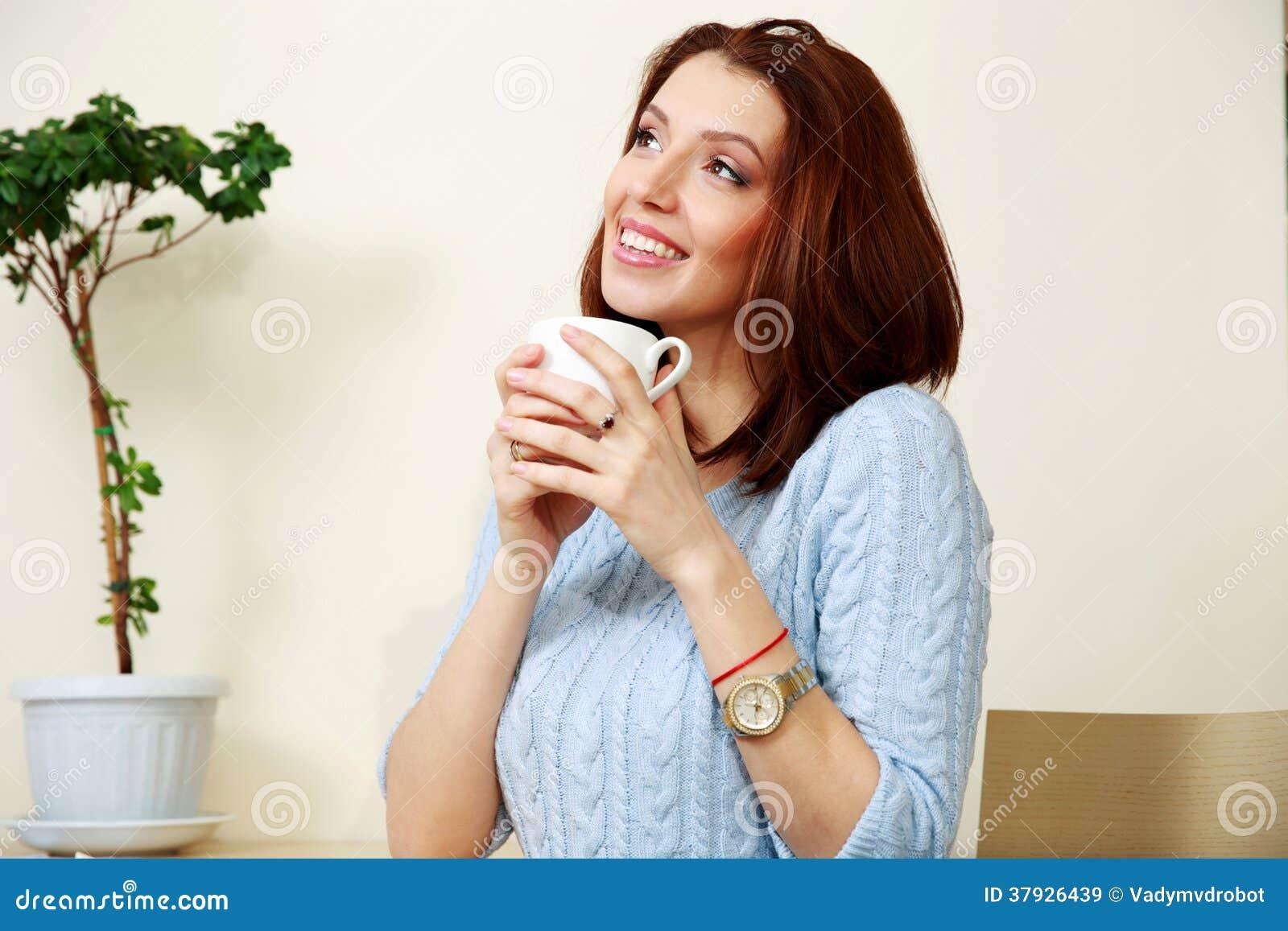 Заботливая женщина держа чашку с кофе