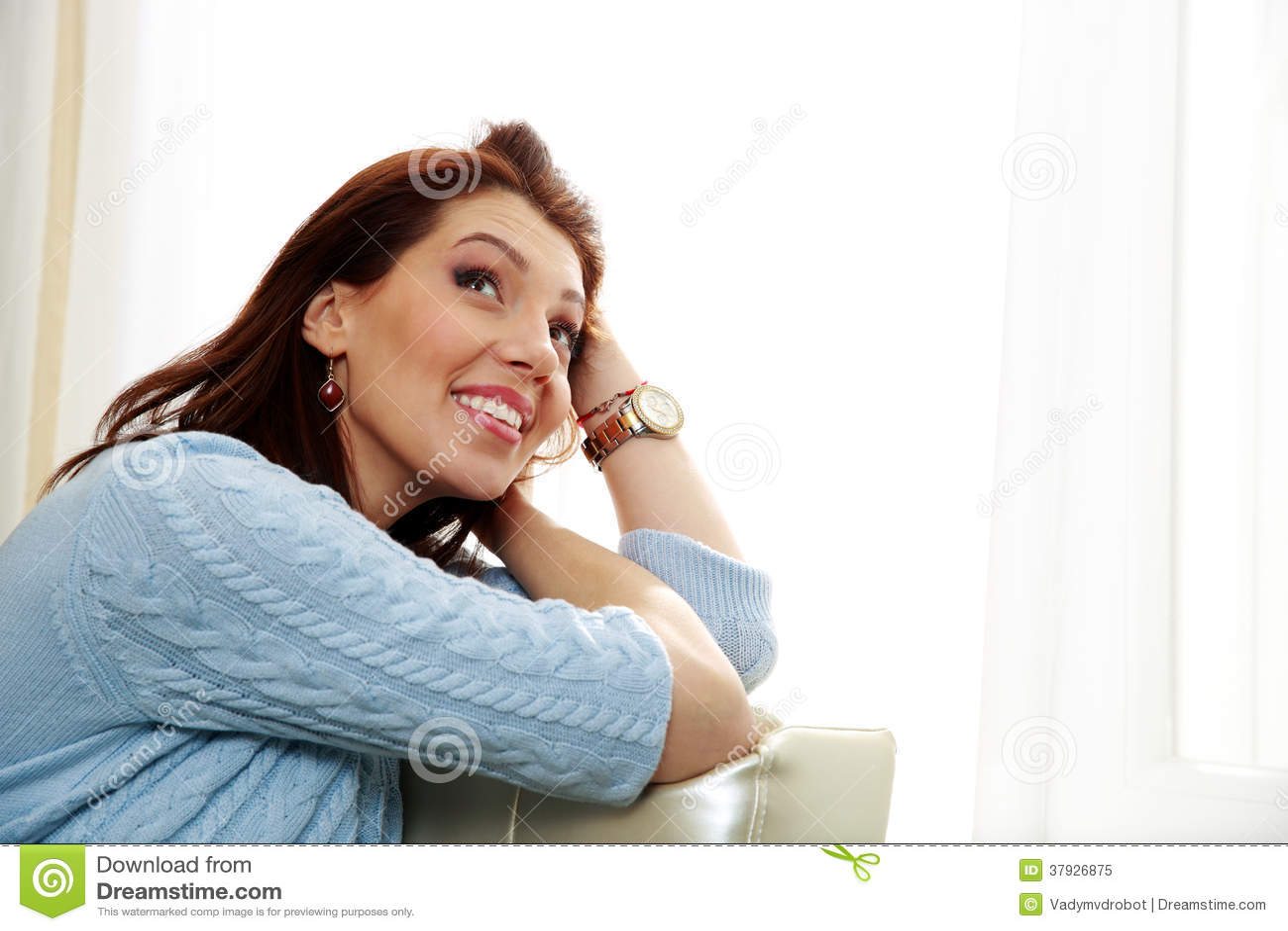 Заботливая женщина сидя на софе и смотря вверх