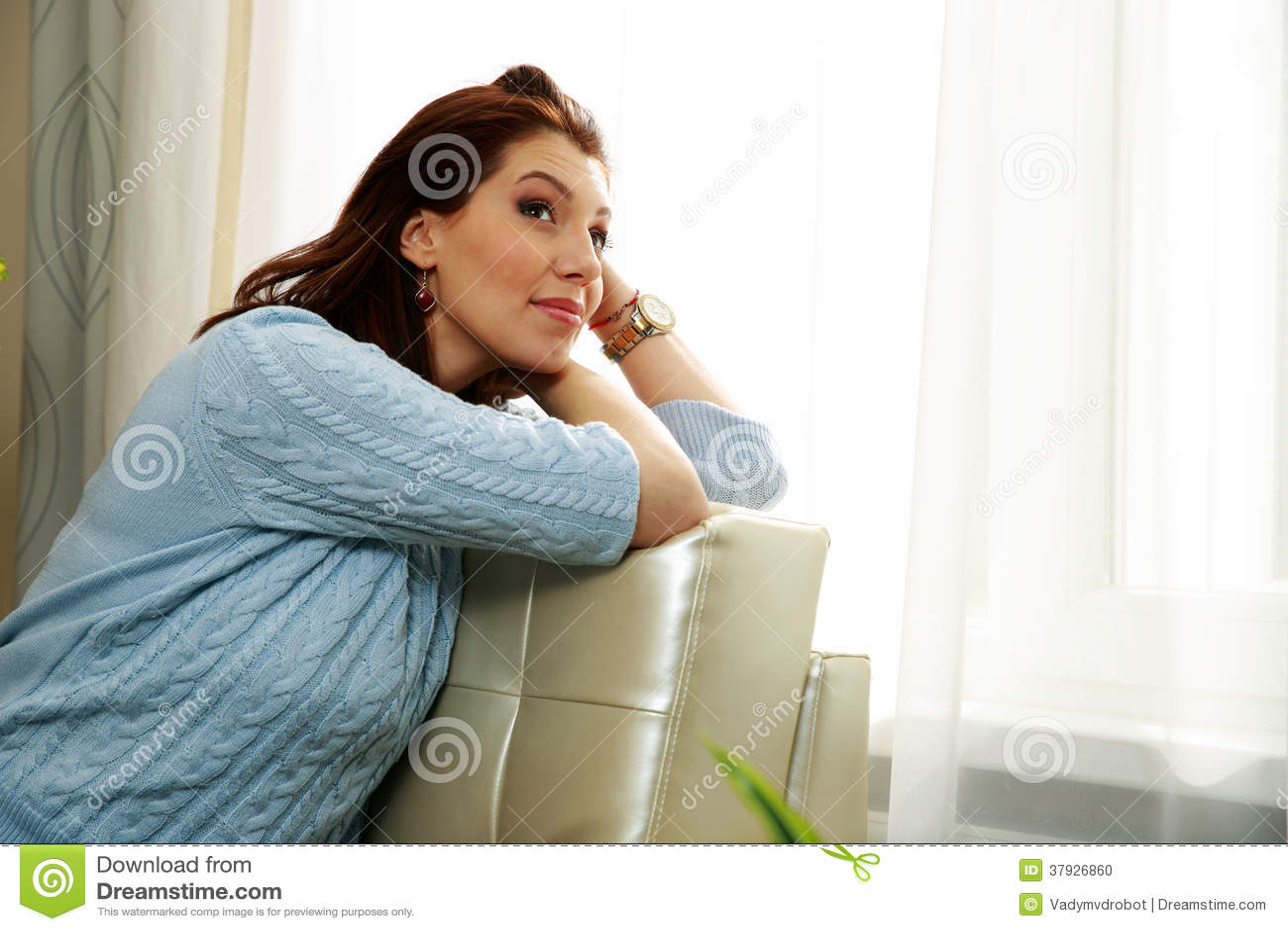 Заботливая женщина сидя на софе