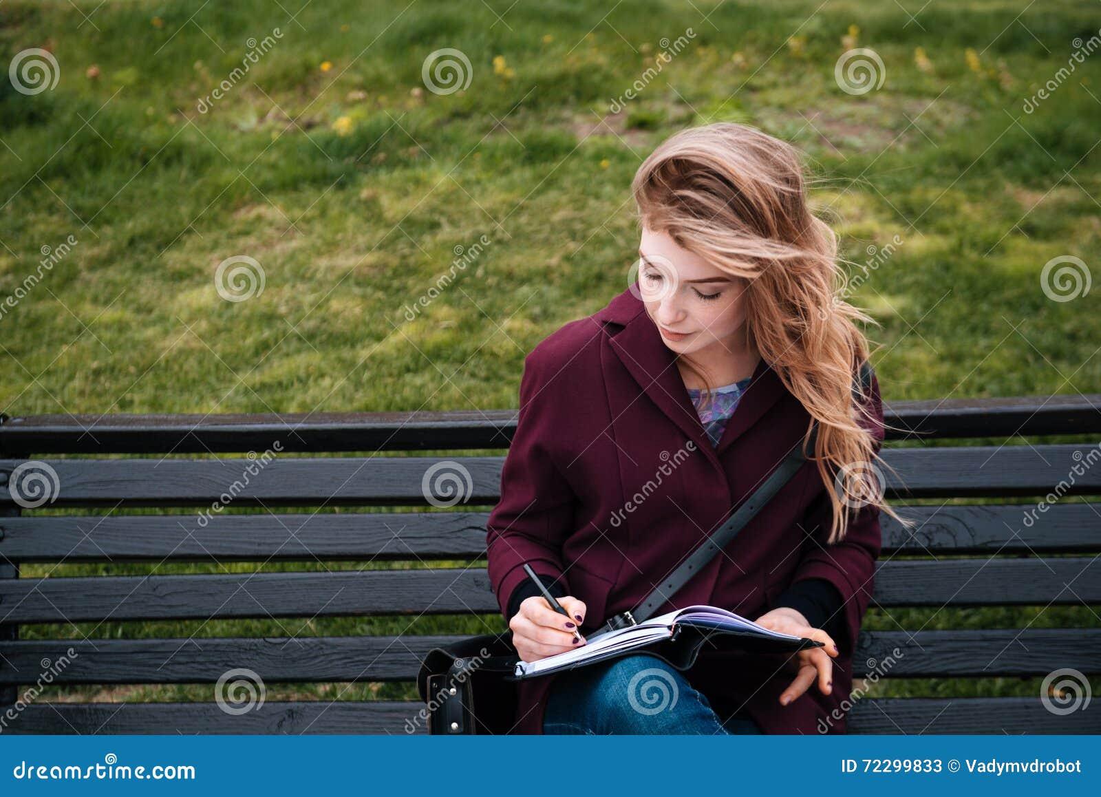 Download Заботливая женщина сидя на стенде и писать в тетради Outdoors Стоковое Изображение - изображение насчитывающей одно, стенд: 72299833