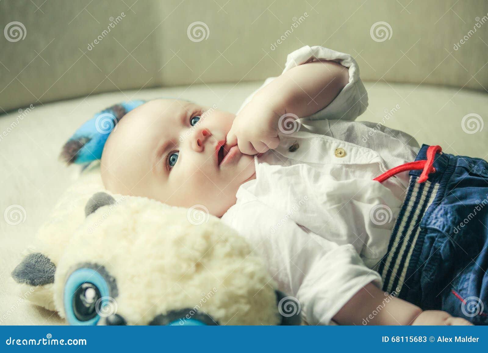 Заботливый маленький ребёнок всасывает палец в рте