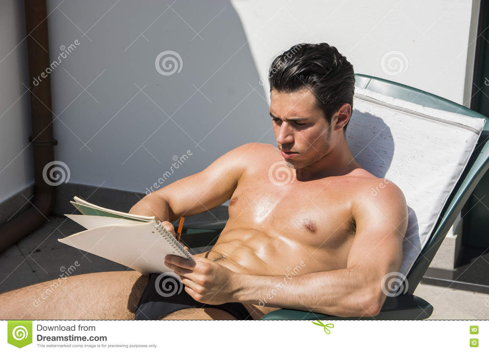 Заботливый топлесс молодой человек в deckchair с карандашем и тетрадью